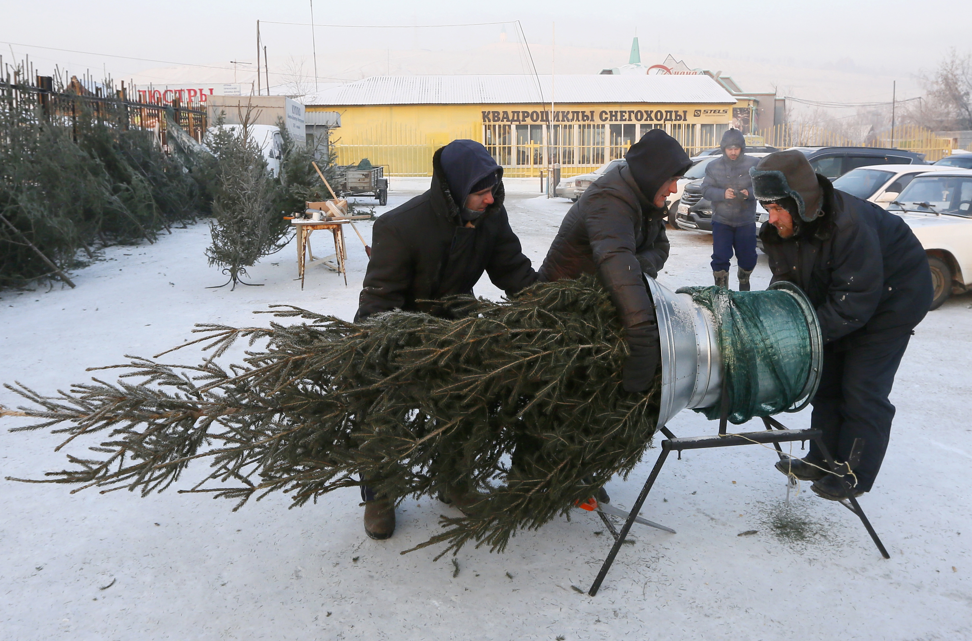 People shop for a New Year's tree at a street market with the air temperature of about -28 degrees Celsius in Krasnoyarsk, Siberia, Dec. 27, 2018.