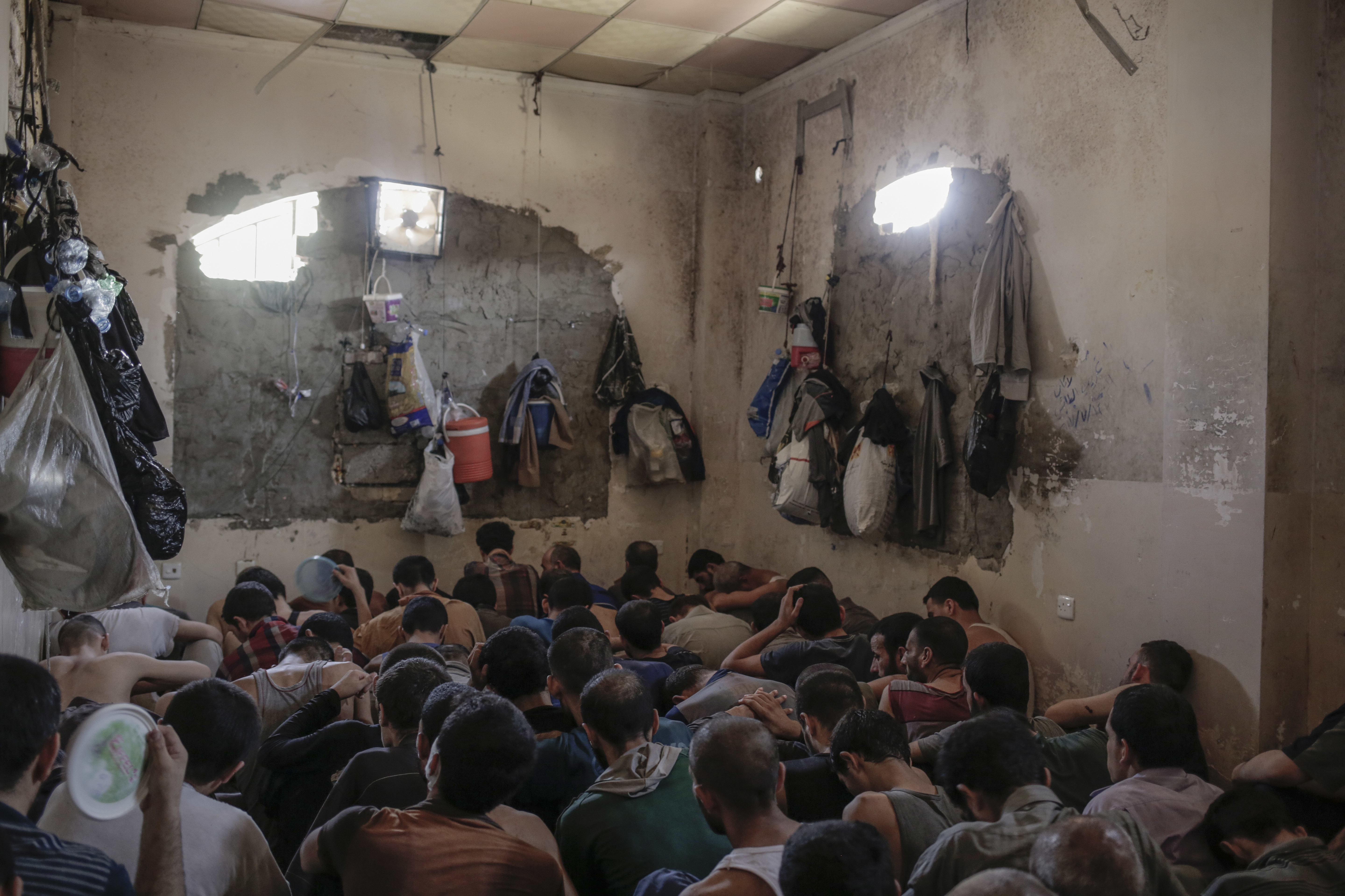 FILE - More than 100 Islamic State suspects sit inside a small room in a prison south of Mosul, July 18, 2017.