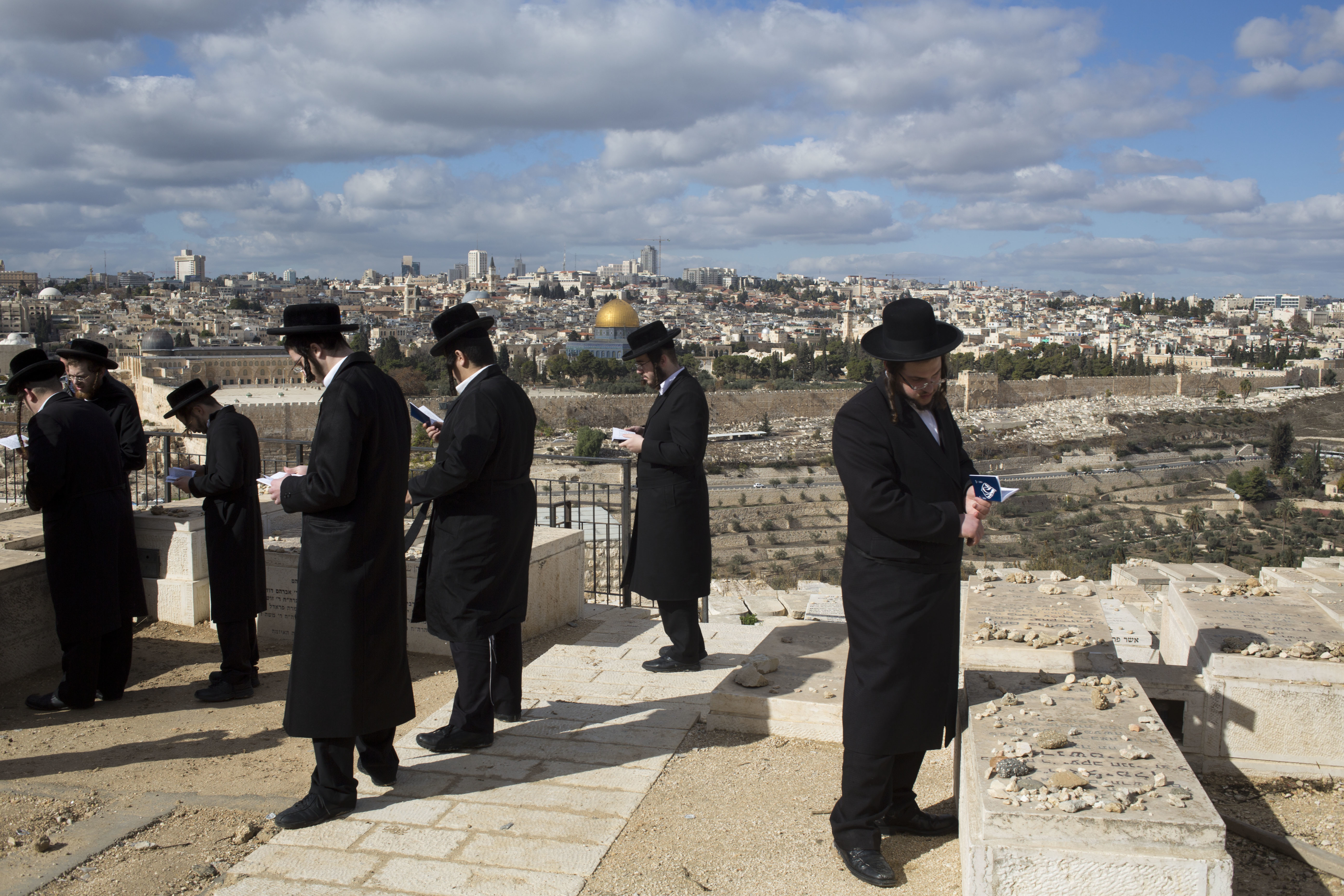 Jerusalem's Old City is seen while Jewish Orthodox men pray in a cemetery in Jerusalem, Dec. 7, 2017, a day after U.S. President Donald Trump's recognition of Jerusalem as Israel's capital.