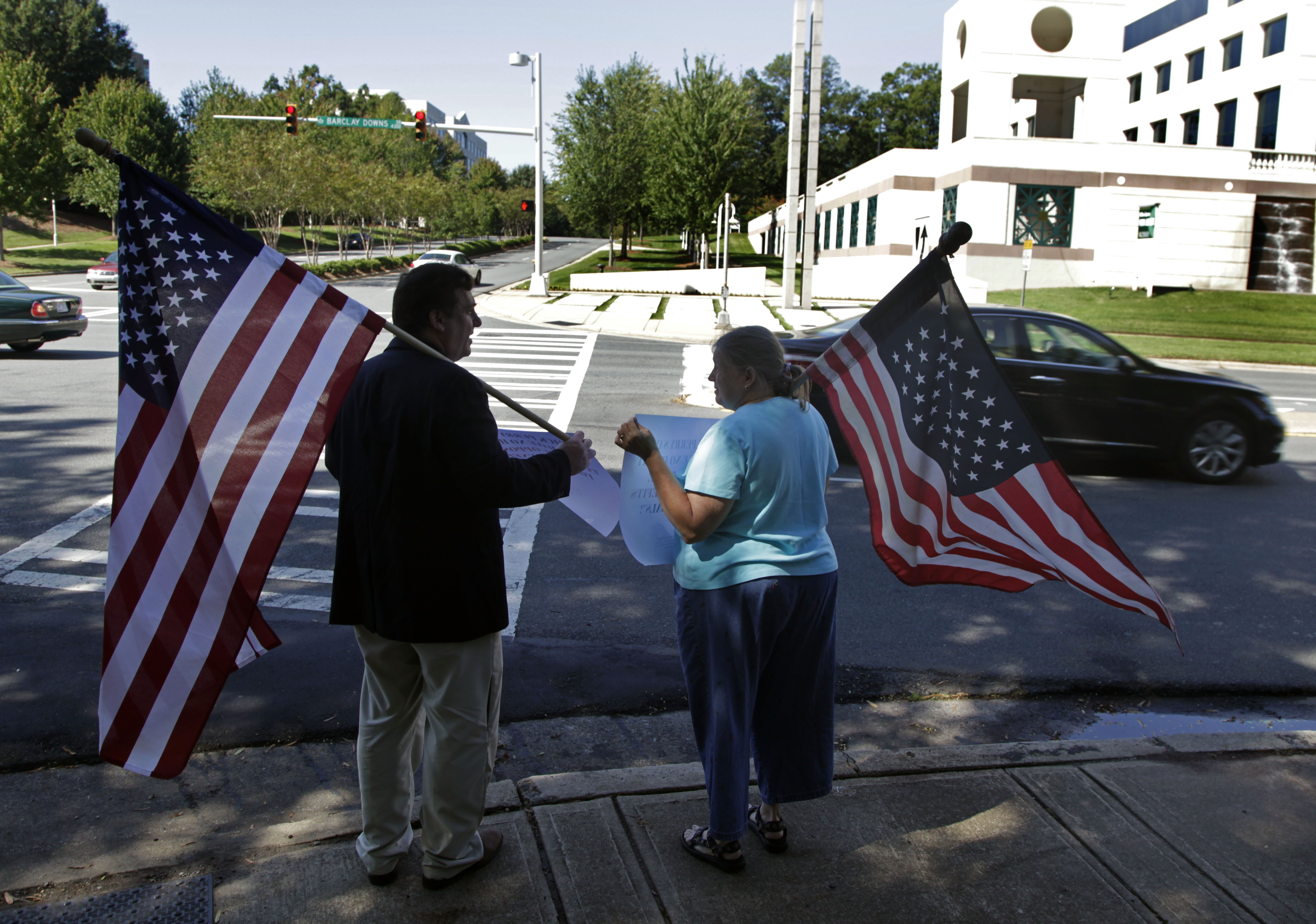 William Gheen, left, president of the political action committee ALIPAC, protests near a fundraiser for Gov. Rick Perry in Charlotte, North Carolina, Sept. 29, 2011. The group was protesting Perry's support of in-state tuition for illegal aliens.