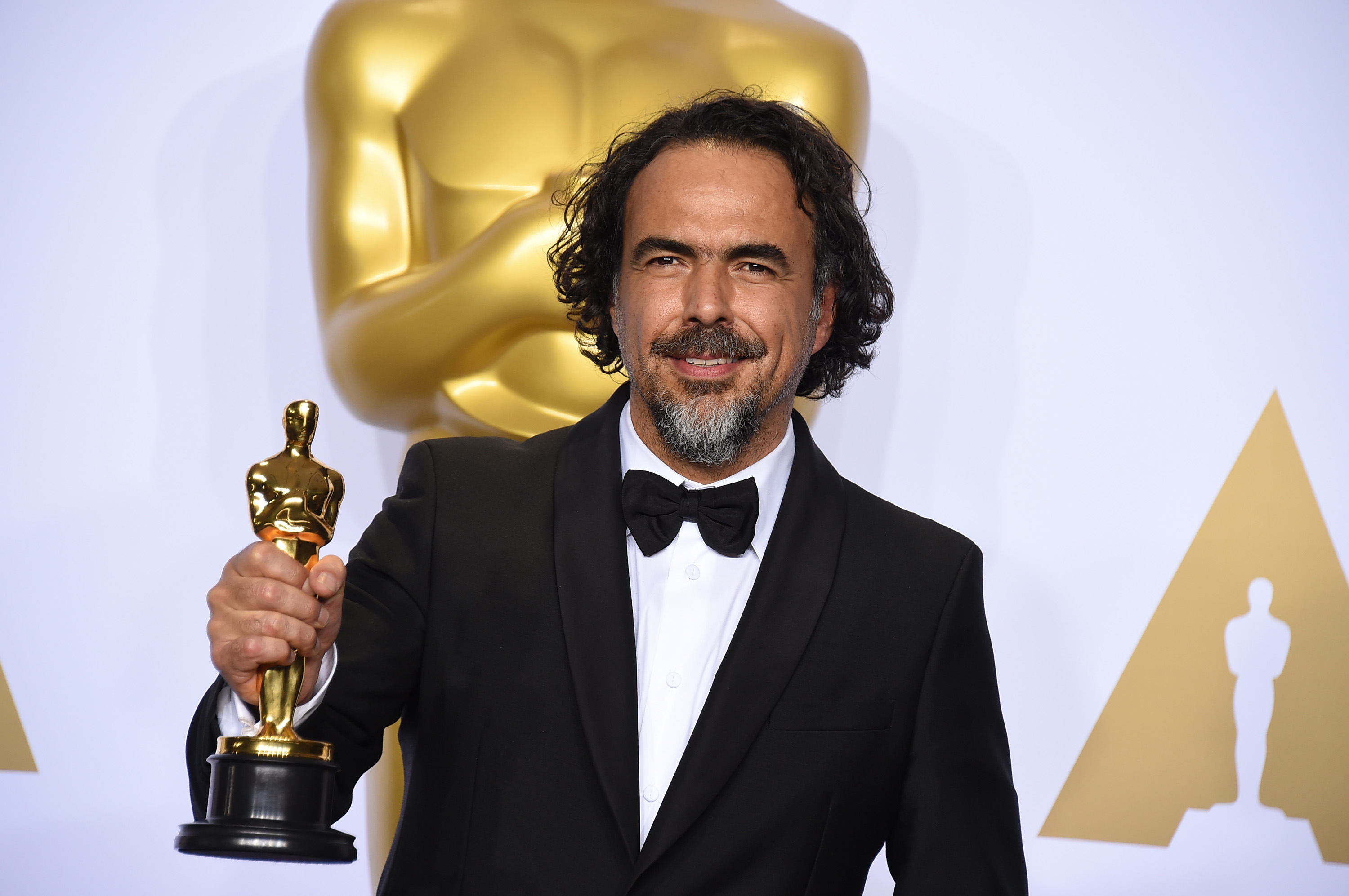 """Alejandro G. Inarritu poses in the press room with the award for best director for """"The Revenant"""" at the Oscars on Feb. 28, 2016, at the Dolby Theatre in Los Angeles."""