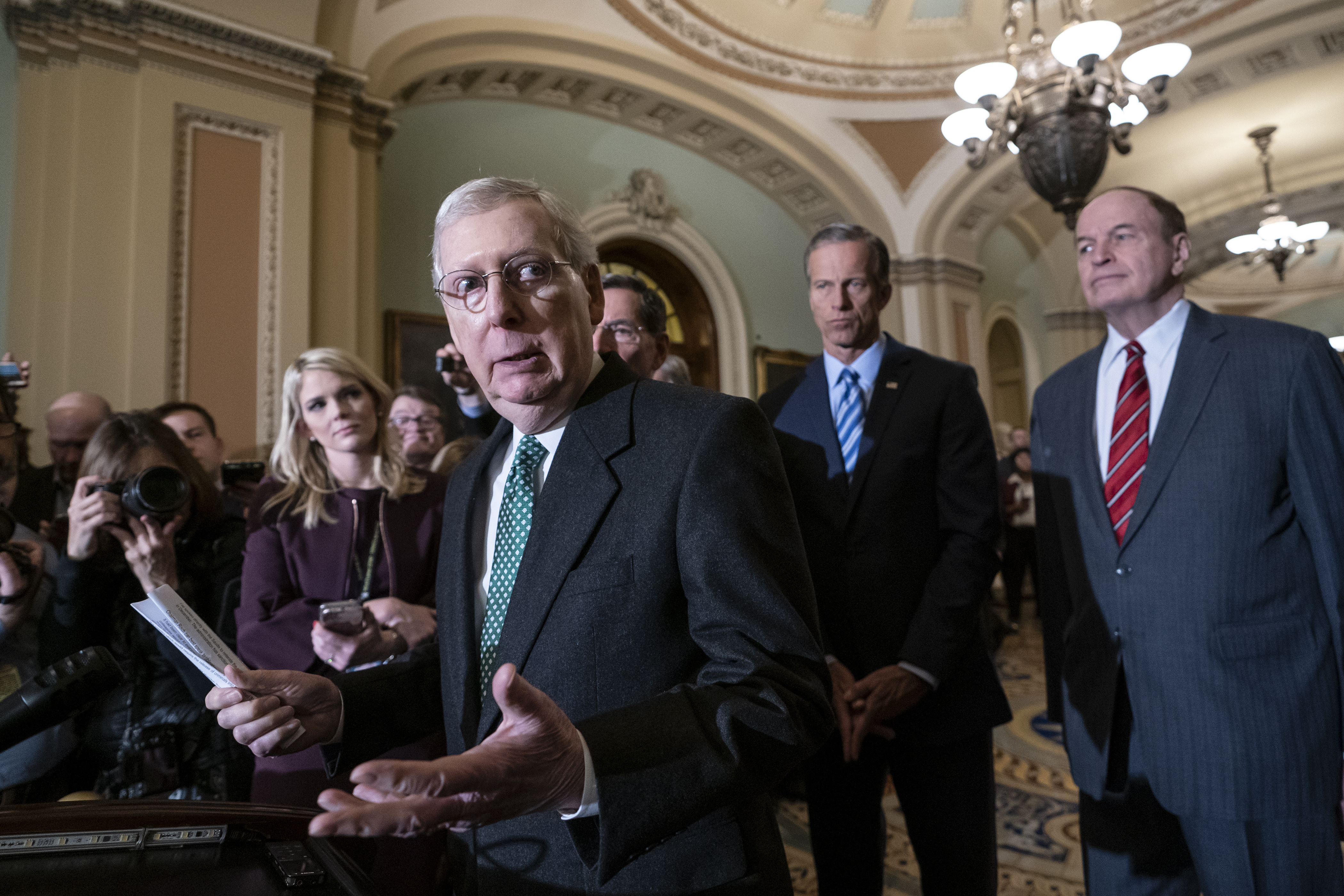 Senate Majority Leader Mitch McConnell, R-Ky., left, speaks to reporters at the Capitol in Washington, Feb. 12, 2019.