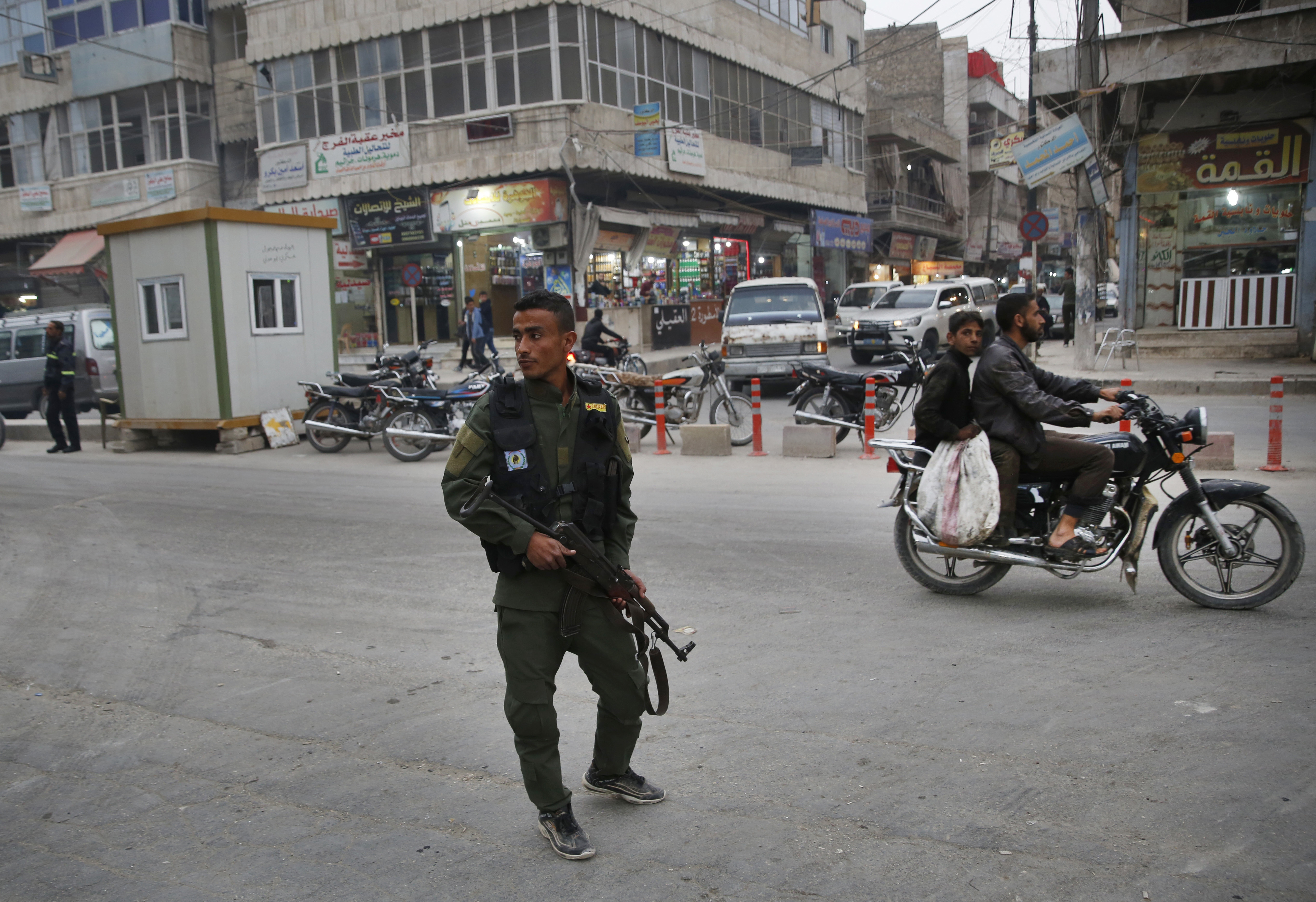 A member of the Kurdish internal security forces patrols a commercial street in Manbij, north Syria, March 28, 2018. Manbij, a mixed Arab and Kurdish town of nearly 400,000, was liberated from Islamic State militants in 2016 by the YPG fighters with