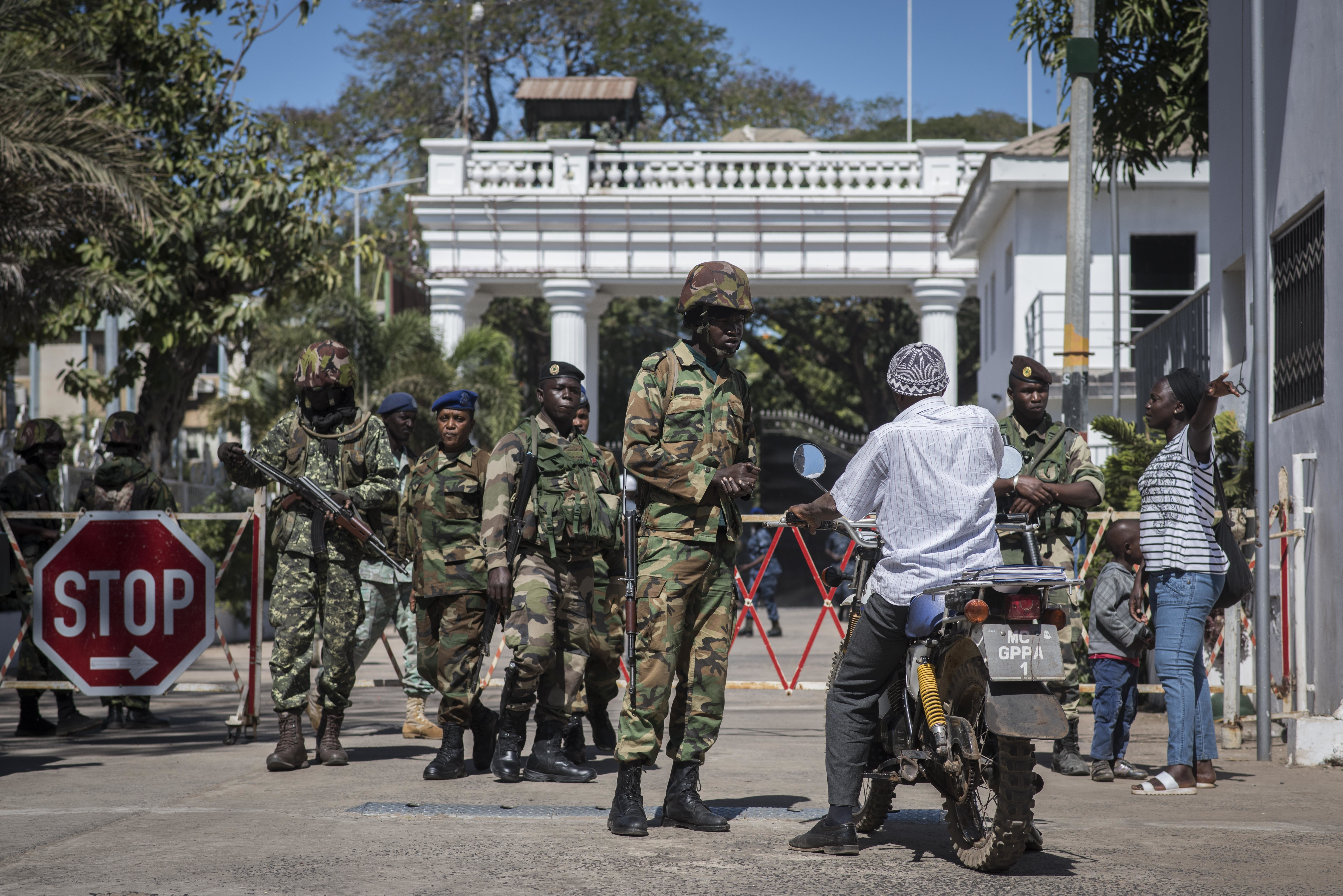 Senegalese soldiers check a motorcyclist at the entrance of the State House compound in Banjul, Gambia, Jan. 24, 2017. ECOWAS troops have moved into the State House to prepare for the return of President Adama Barrow.