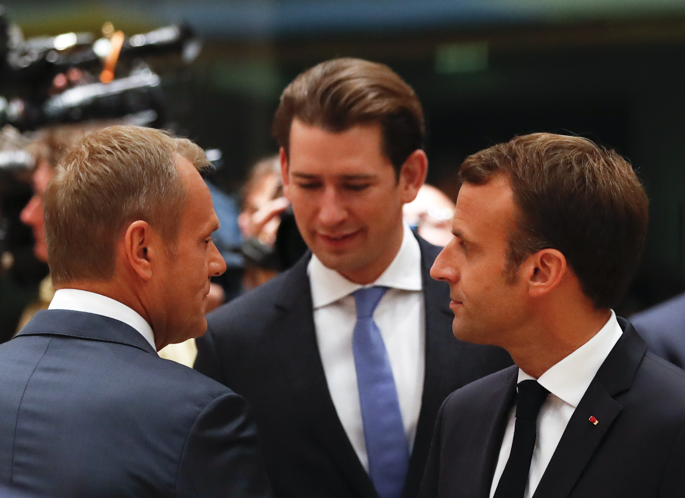 European Council President Donald Tusk, left, speaks with Austrian Chancellor Sebastian Kurz, center, and French President Emmanuel Macron during a round table meeting at an EU summit in Brussels,  Oct. 17, 2018.