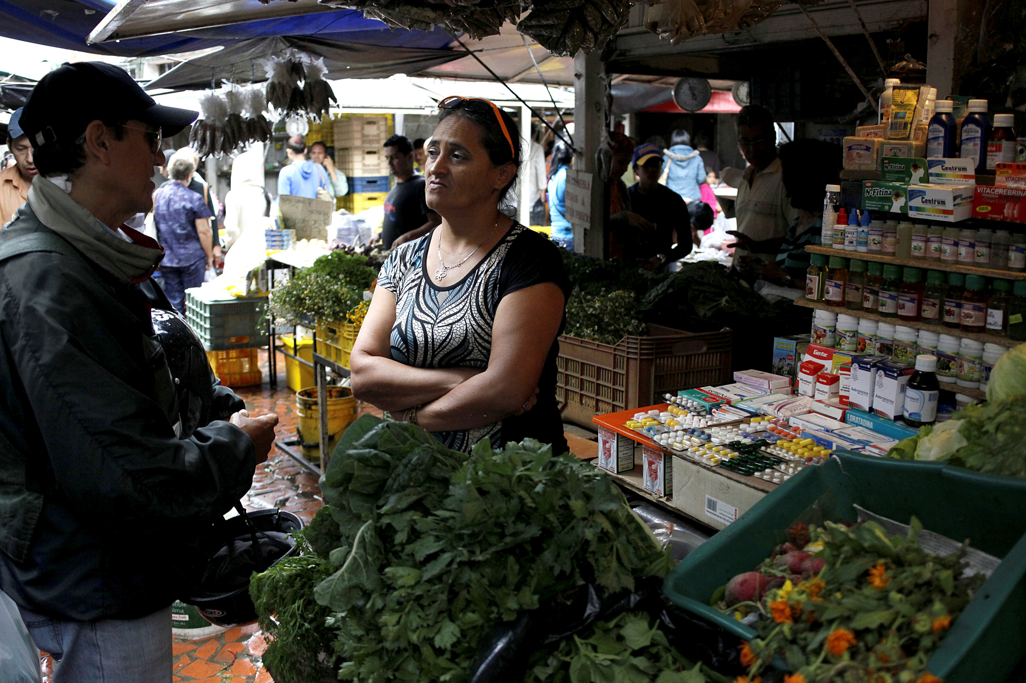 A vendor talks with a customer in her fruit and vegetables stall selling medicines at a market in Rubio, Venezuela, Dec. 5, 2017.