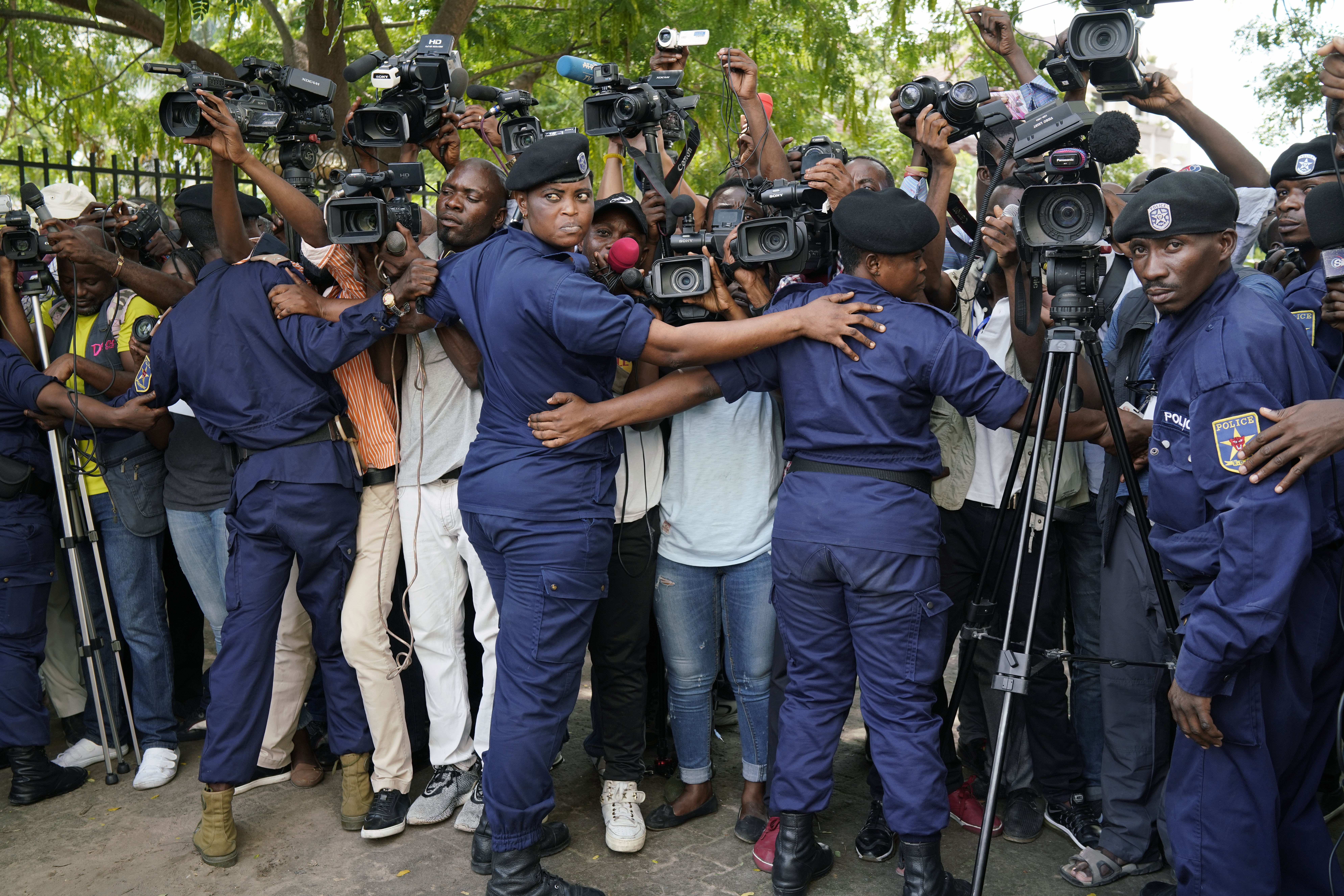FILE - Congolese police officers hold back members of the media as Congo opposition candidate Martin Fayulu leaves the constitution court in Kinshasa, Congo, Jan. 12, 2019.
