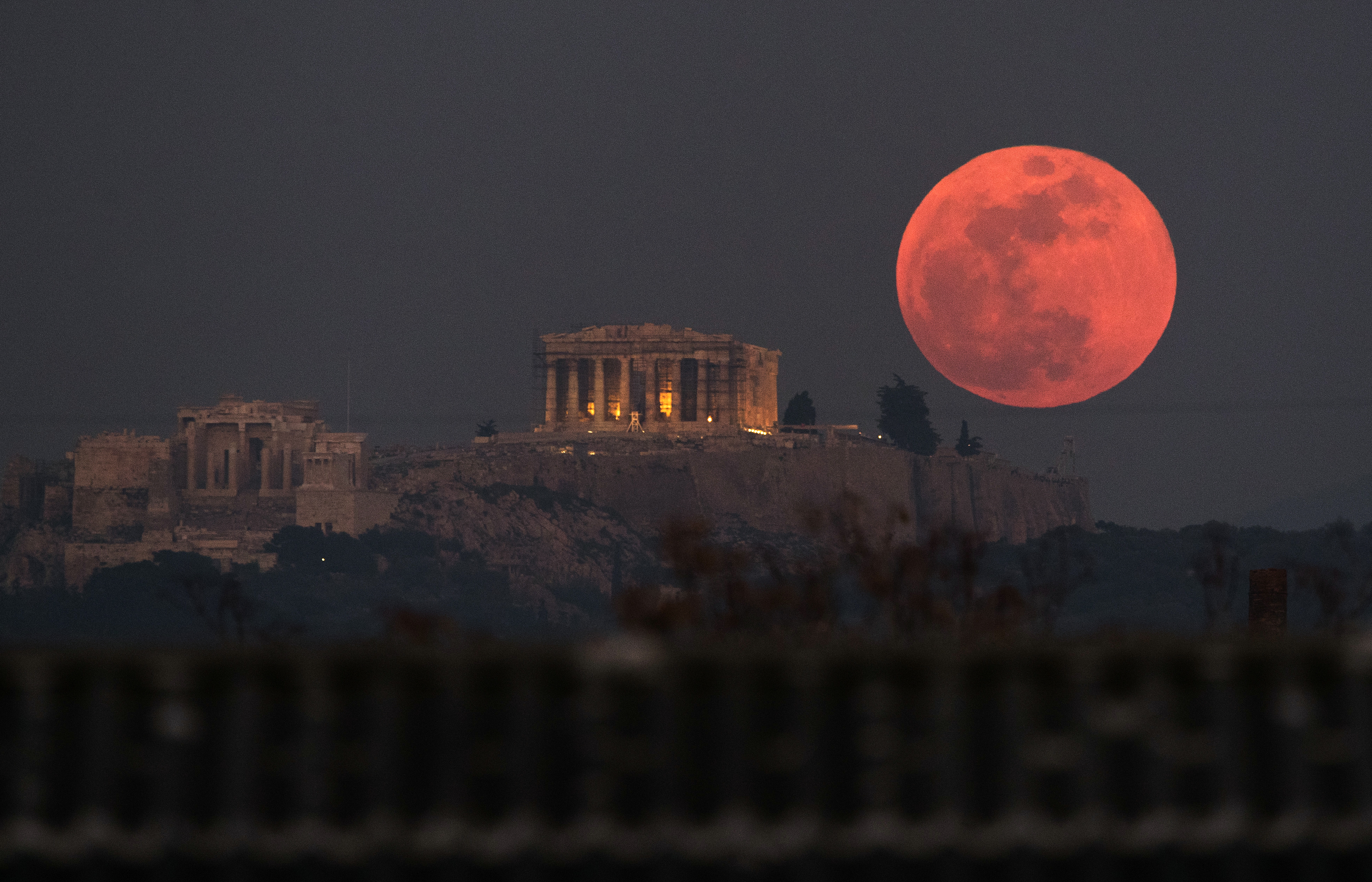 A super blue blood moon rises behind the 2,500-year-old Parthenon temple on the Acropolis of Athens, Greece, Jan. 31, 2018.
