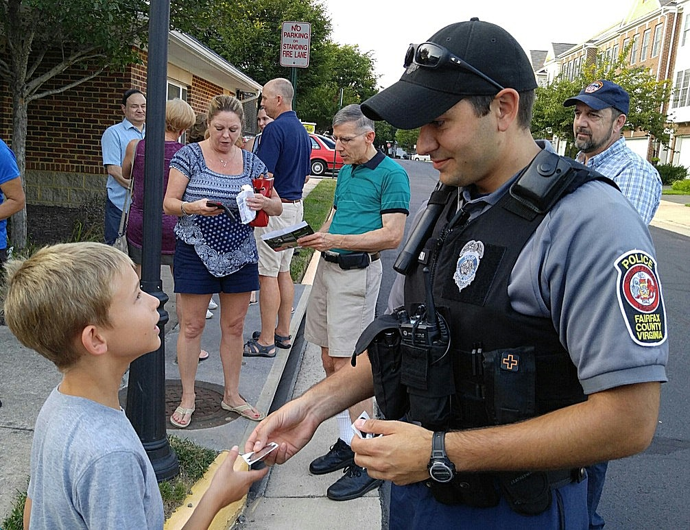 """A boy gets a """"junior"""" police badge during National Night Out in Fairfax Country, Virginia, Aug. 2, 2016. (D. Block/VOA)"""
