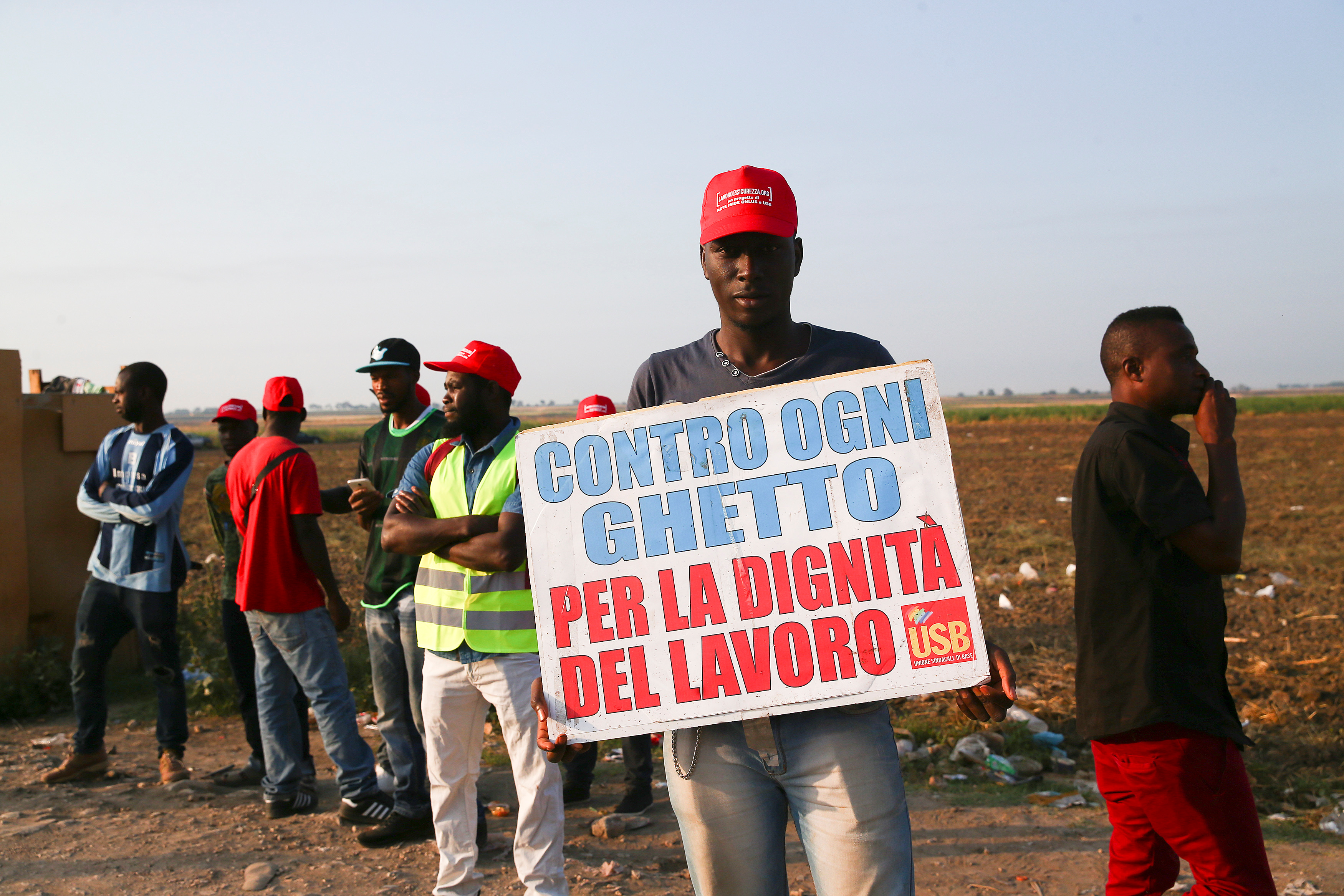 "An African migrant laborer holds a banner reading ""against all ghetto, for the dignity of work"" during a march to protest against his work conditions in Italy, following the death of 16  colleagues in two separate road accidents, near Foggia, Italy, ..."