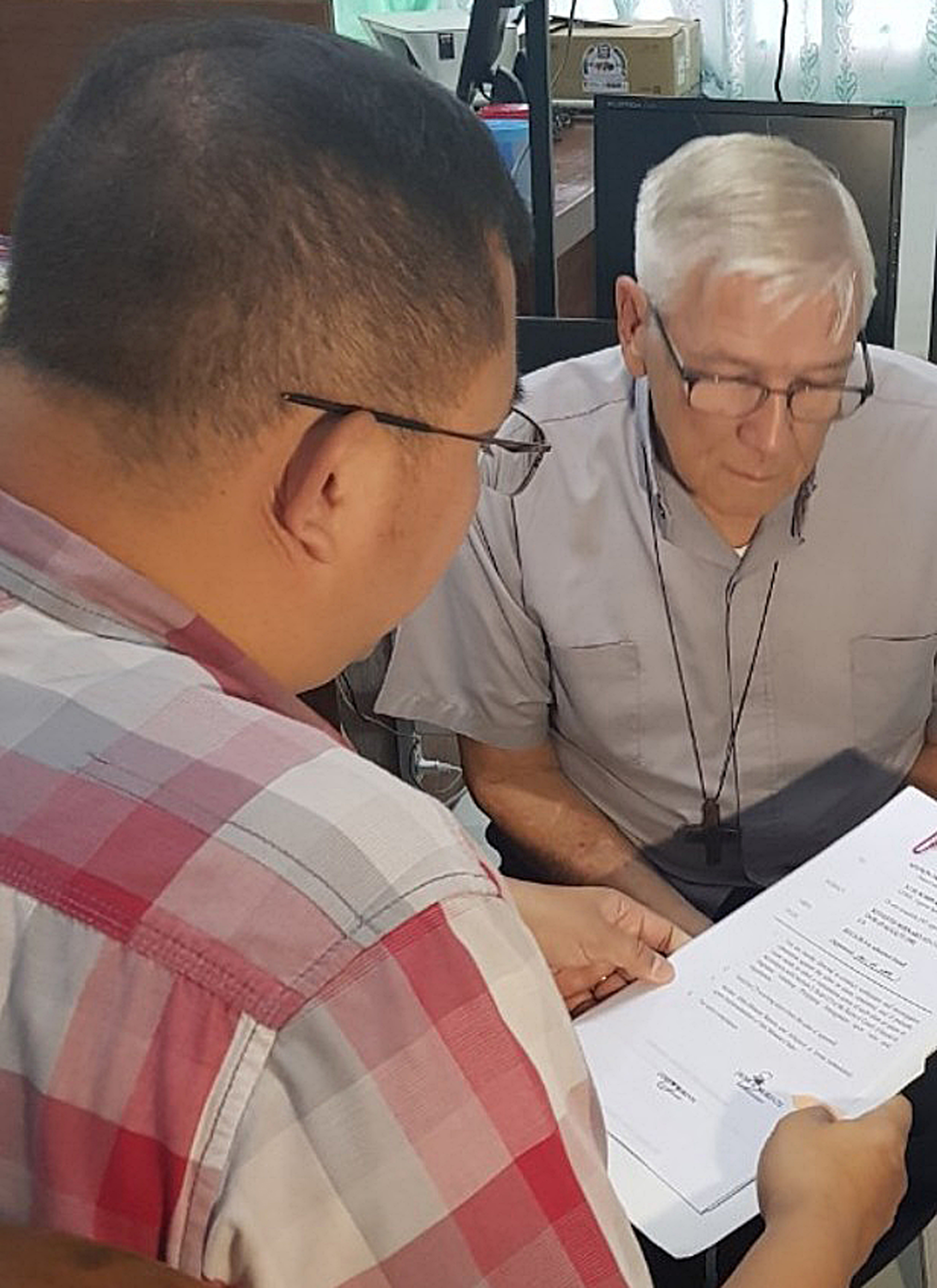 In this Bureau of Immigration photo, an American Roman Catholic priest, the Rev. Kenneth Bernard Hendricks, right, looks at documents after being arrested in a church in Naval in the island province of Biliran, central Philippines, Dec. 5, 2018.