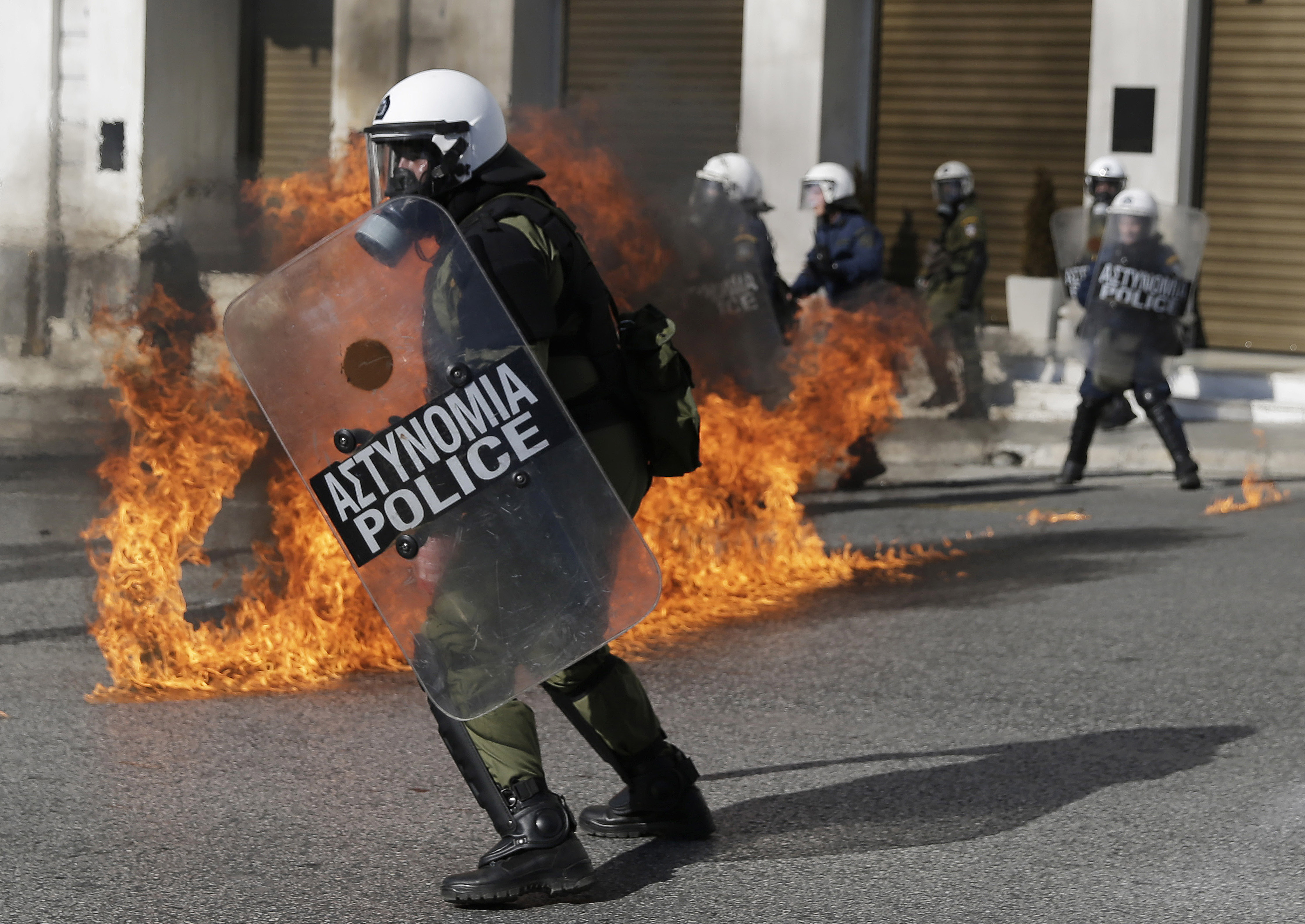 Riot policemen dodge petrol bombs thrown by protesters Nov. 12, 2015, during a rally in Athens. Clashes have broken out as the country faces its first general strike since the Greece's left-led government came to power in January.