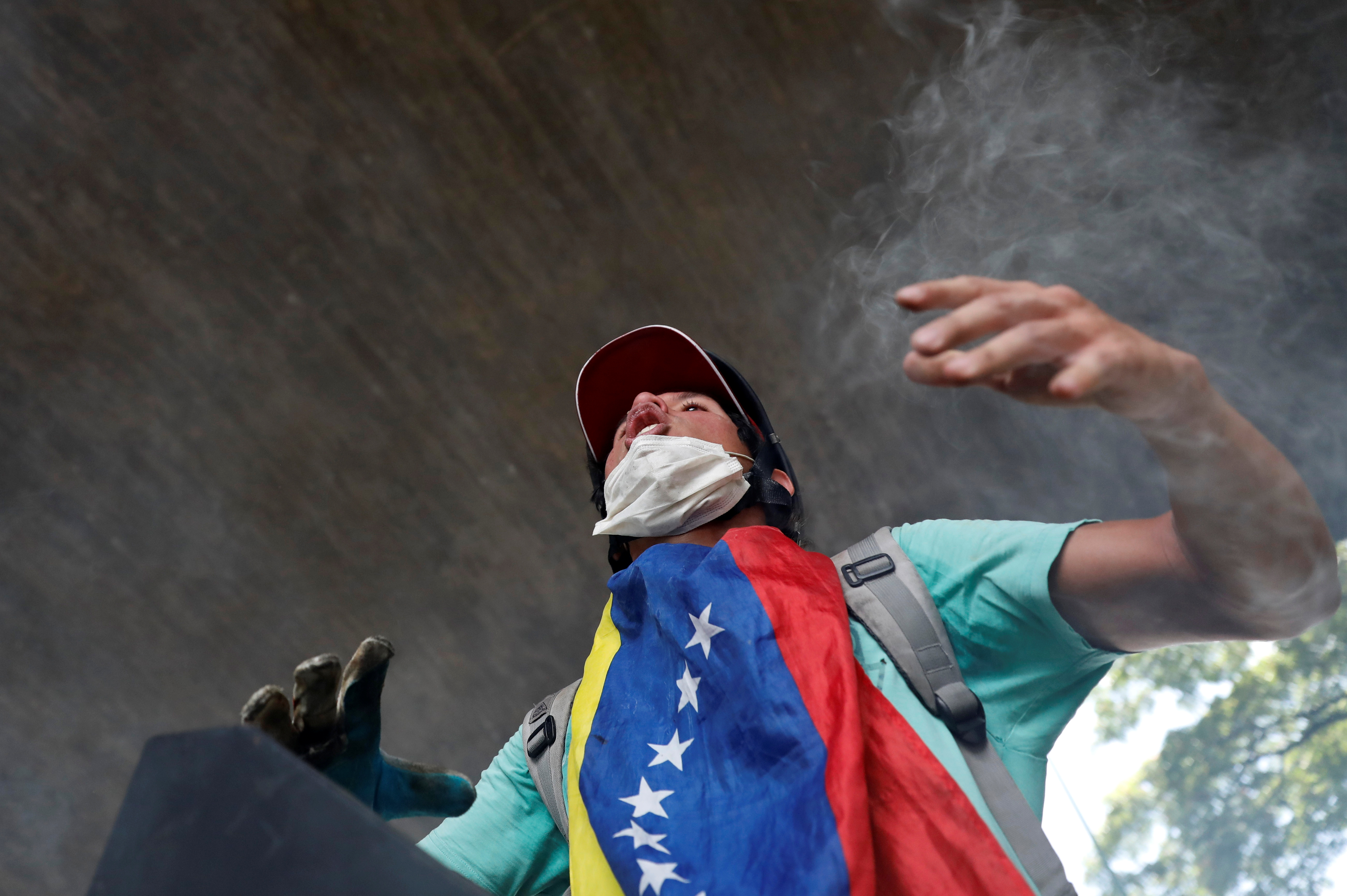 An opposition supporter clashes with riot police while rallying against President Nicolas Maduro in Caracas, Venezuela, May 4, 2017.