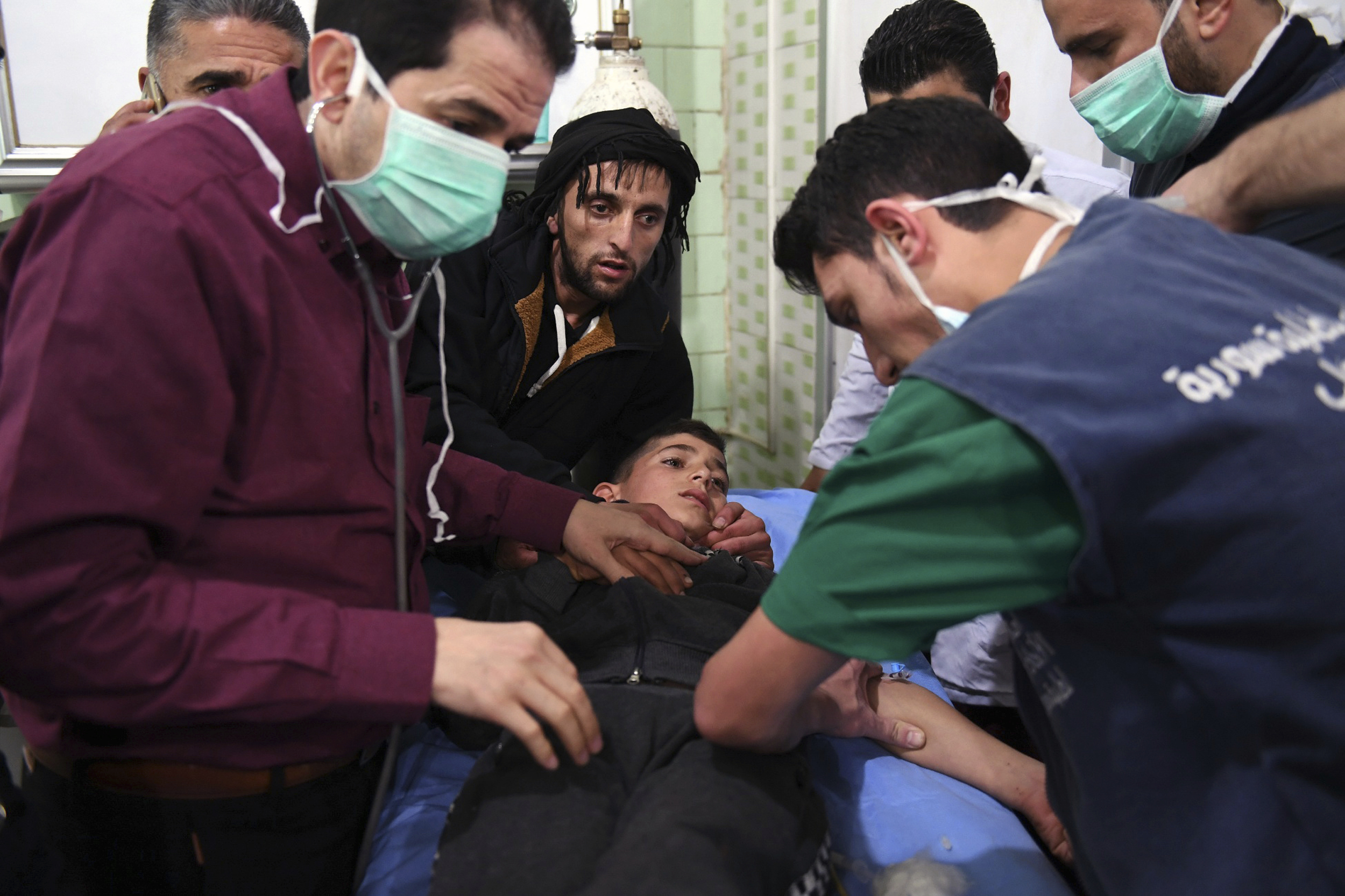 This photo released by the Syrian official news agency SANA shows medical staff treating a boy following a suspected chemical attack on his town of al-Khalidiya, in Aleppo, Syria, Nov. 24, 2018.