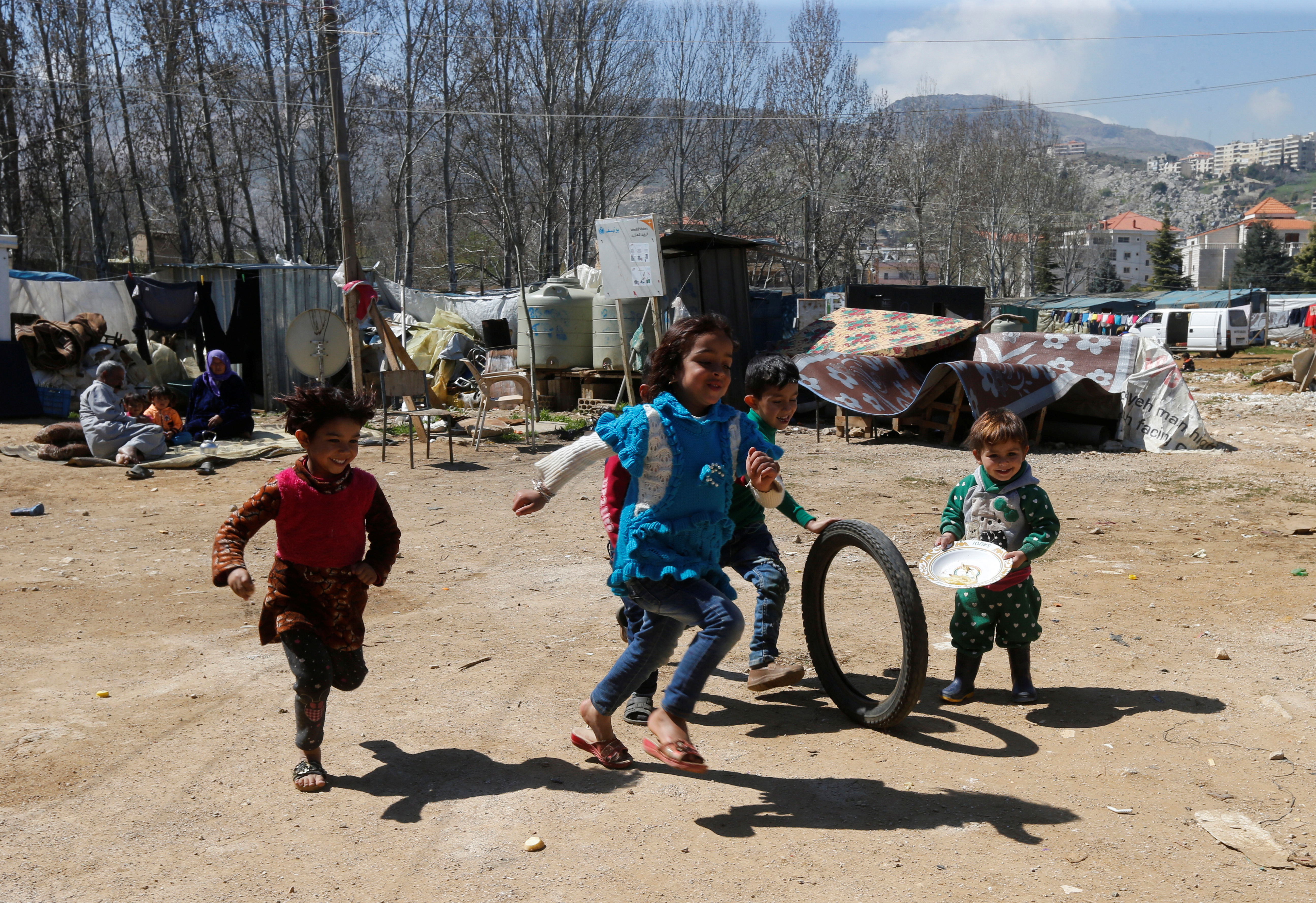 Syrian refugee children run in a tented settlement, in the town of Qab Elias, in Lebanon's Bekaa Valley, March 13, 2018.