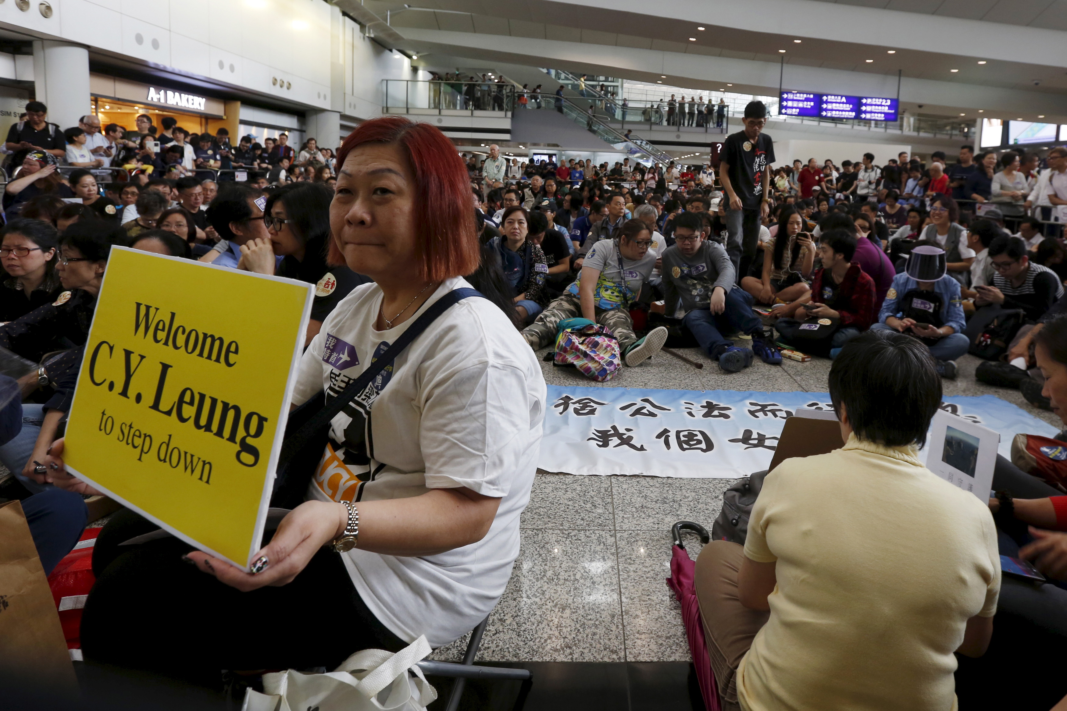 FILE - A protester carries a placard as hundreds of airlines related staff and citizens protest against Hong Kong Chief Executive Leung Chun-ying, who allegedly put pressure on airport staff to help his daughter retrieve a bag left outside of restric...