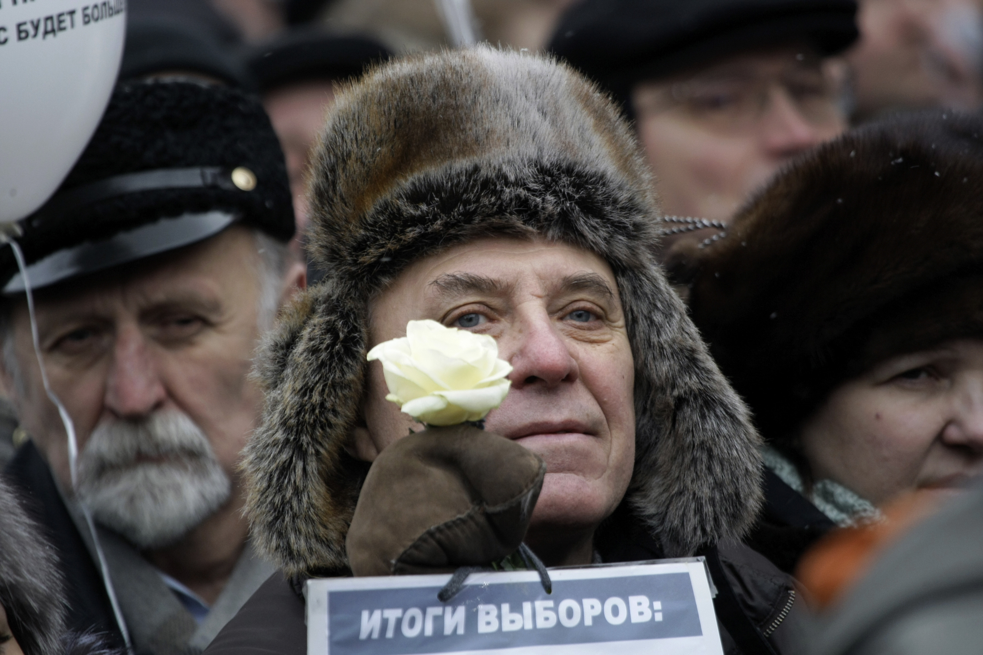 "An elderly protester  holds a white flower as symbol of revolution and a paper with the words ""election results"" during a protest against alleged vote rigging in Russia's parliamentary elections on Sakharov Avenue in Moscow, Dec. 24, 2011.. (AP)"