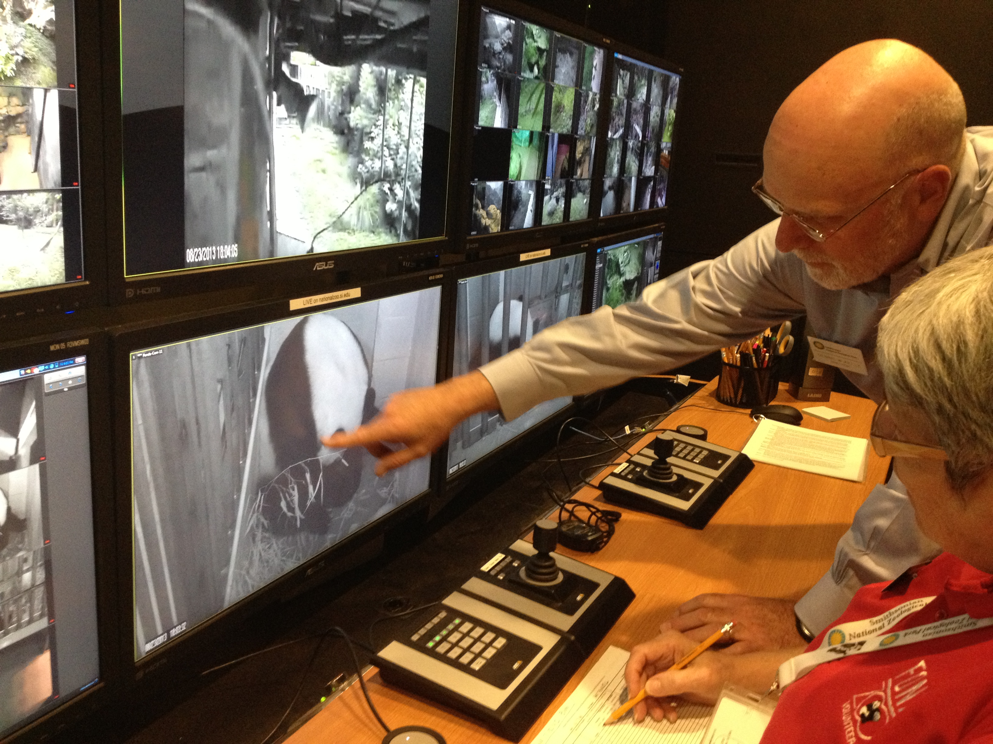 FILE - National Zoo director Dennis Kelly and a webcam volunteer watch Mei Xiang and her new cub, Bao Bao, via the Giant Panda Cam in 2013. (Credit: Smithsonian's National Zoo)