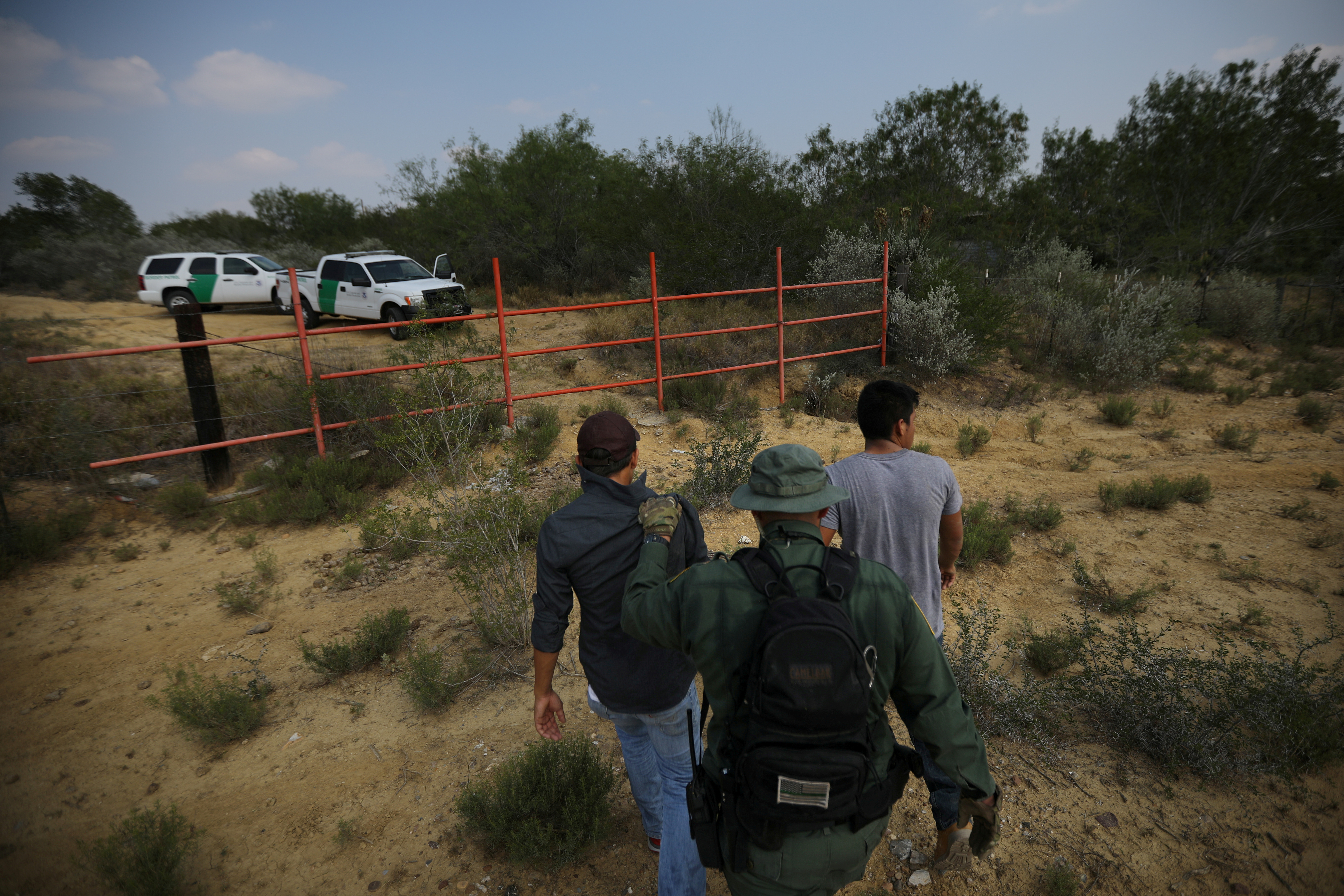 FILE - A US border patrol agent escorts men being detained after entering the United States by crossing the Rio Grande river from Mexico, in Roma, Texas, May 11, 2017.