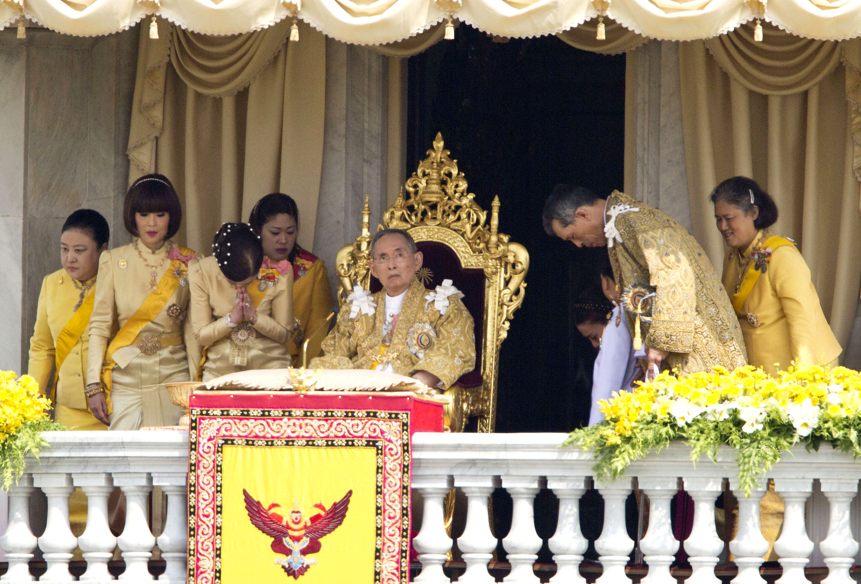 FILE - Thai King Bhumibol Adulyadej, center, is surrounded by his family members (L-R) Princess Somsavali, his daughter Princess Ubolratana, his daughter Princess Chulabhorn, Princess Siribhachudabhorn, Royal Consort Princess Srirasm, his grandson Pr...