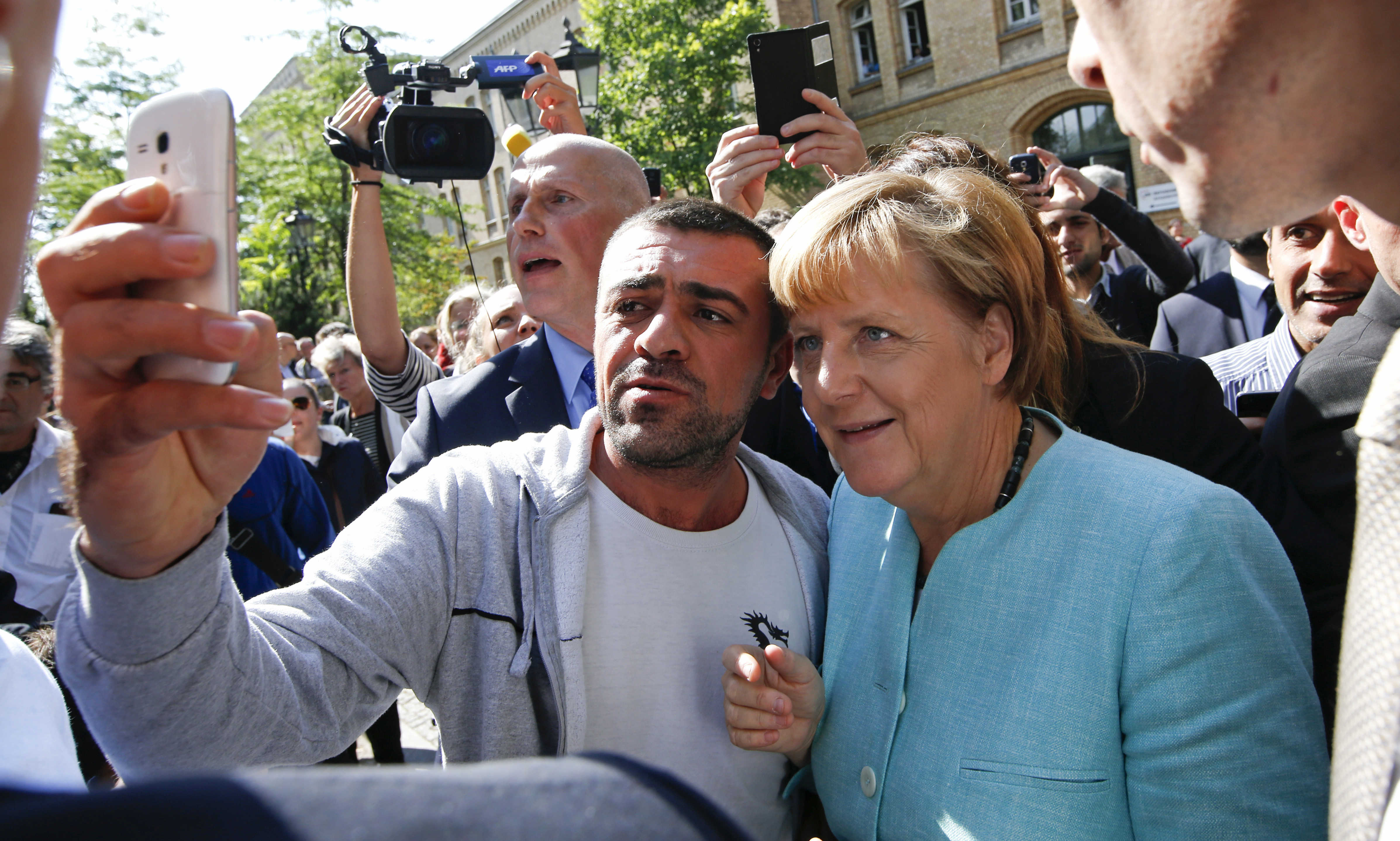 A migrant takes a selfie with German Chancellor Angela Merkel outside a refugee camp near the Federal Office for Migration and Refugees after registration at Berlin's Spandau district, Germany, Sept. 10, 2015.