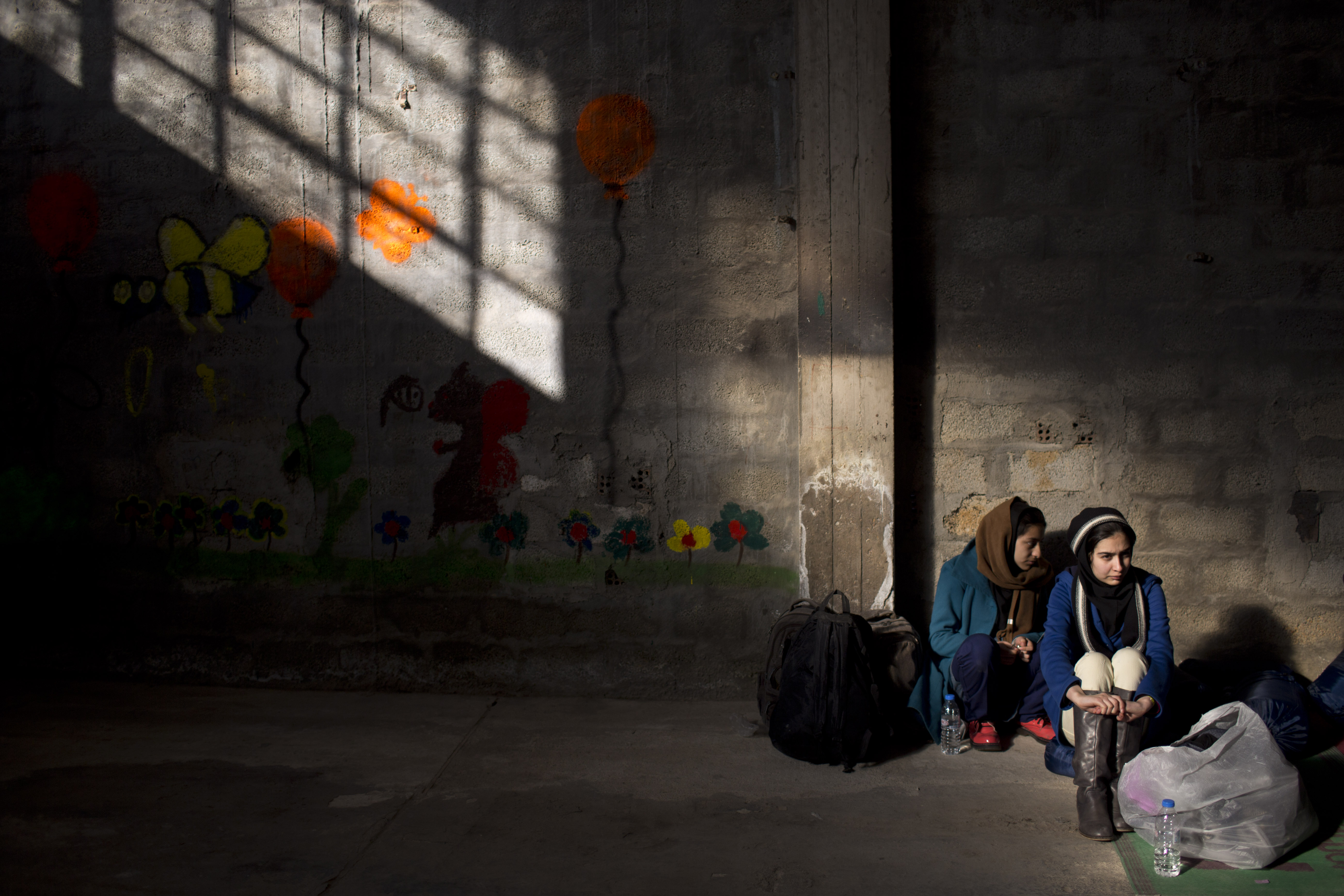Two Afghan young women wait to be registered in the Tabakika registration center, Greece, Jan. 15, 2016.