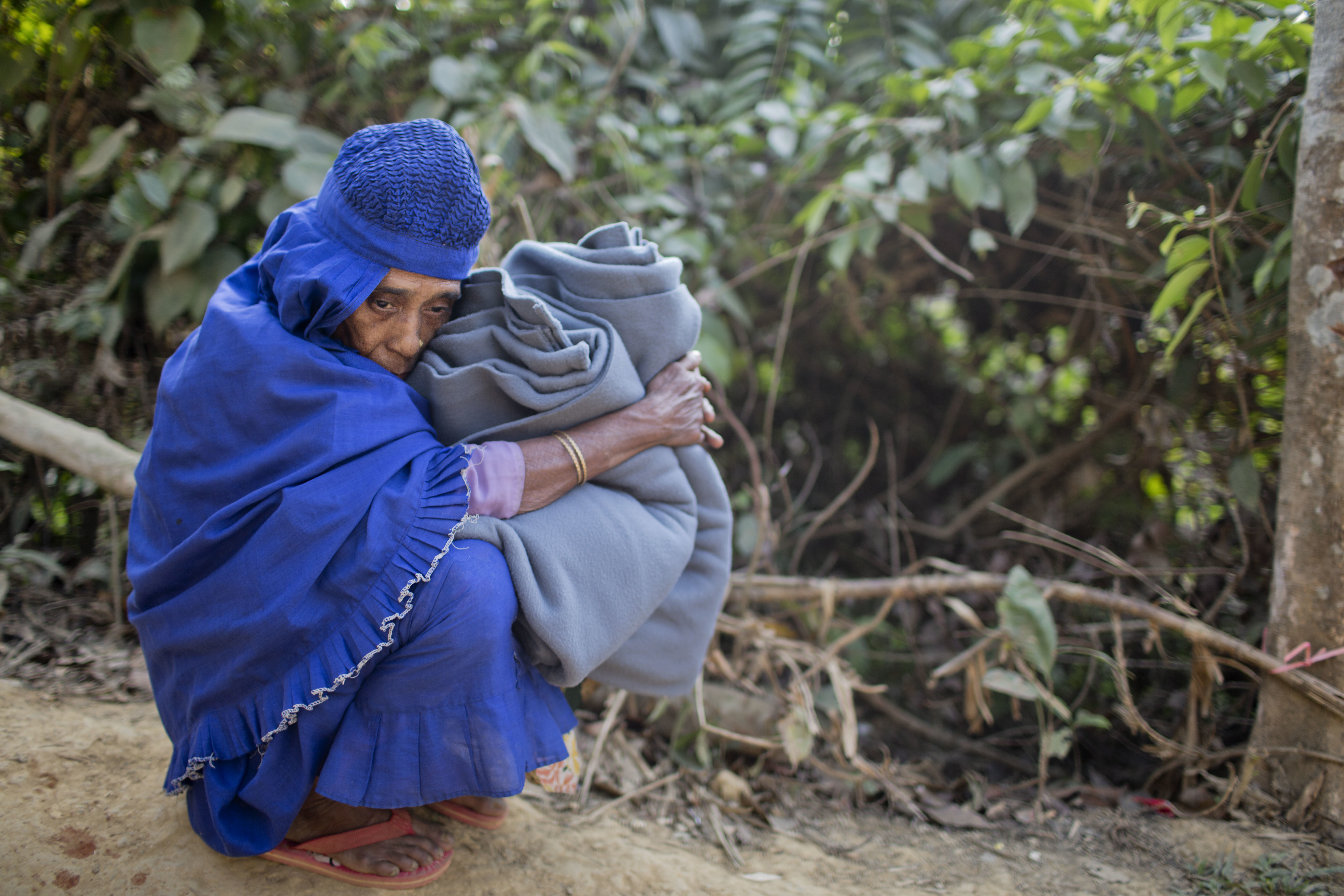 A Rohingya Muslim woman holds on to a blanket and rests on the road after collecting aid at the Kutupalong refugee camp in Ukhiya, Bangladesh, Dec. 21, 2017.  Hundreds of thousands of Rohingya people have crossed over from Myanmar into Bangladesh.