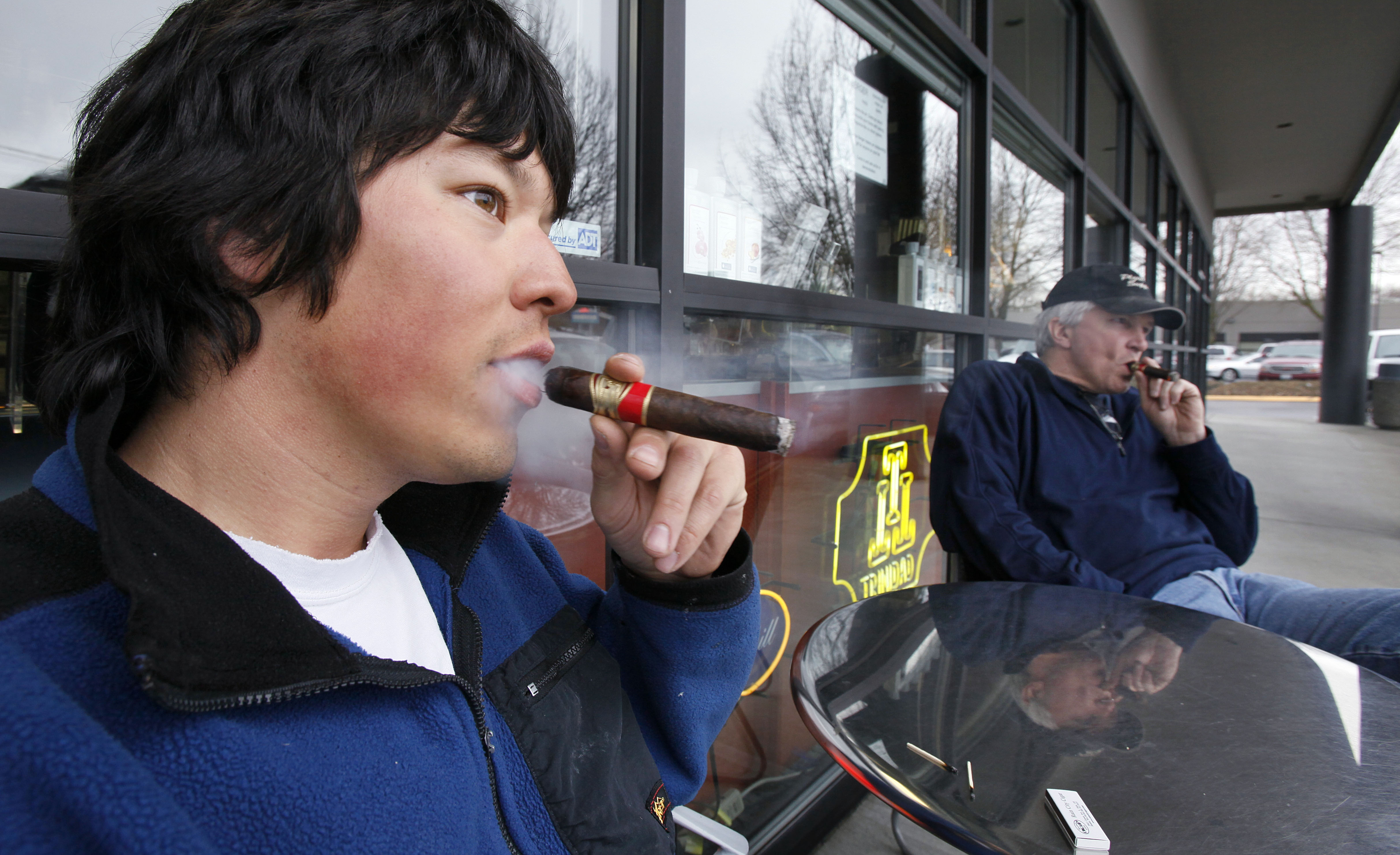 Jameson Florence, left, and Mark Jablonski as they smoke La Traviata cigars outside the Rain City Cigar shop in Seattle.