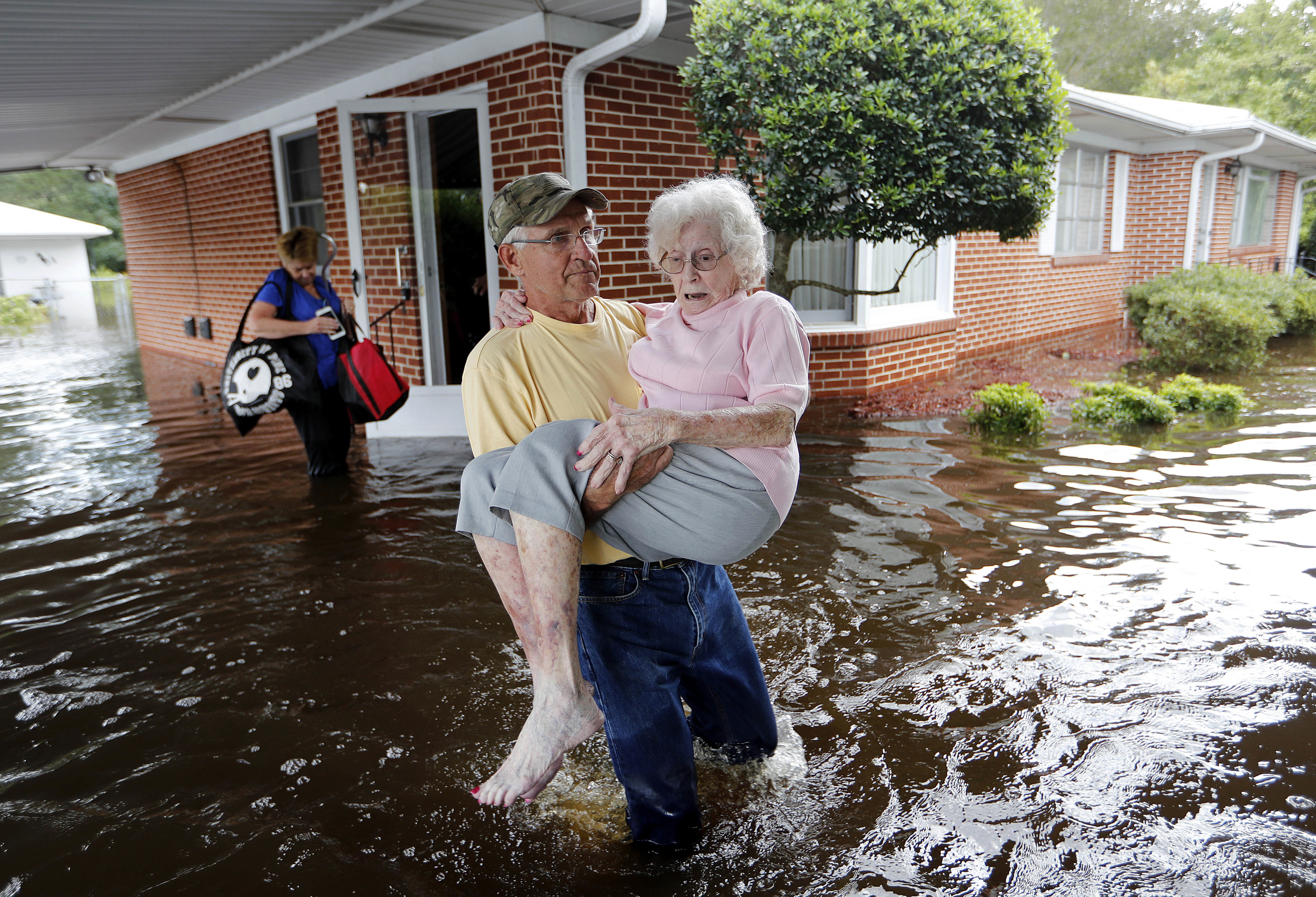 Bob Richling carries Iris Darden, 84, out of her flooded home as her daughter-in-law, Pam Darden, gathers her belongings in the aftermath of Hurricane Florence in Spring Lake, North Carolina, Sept. 17, 2018.
