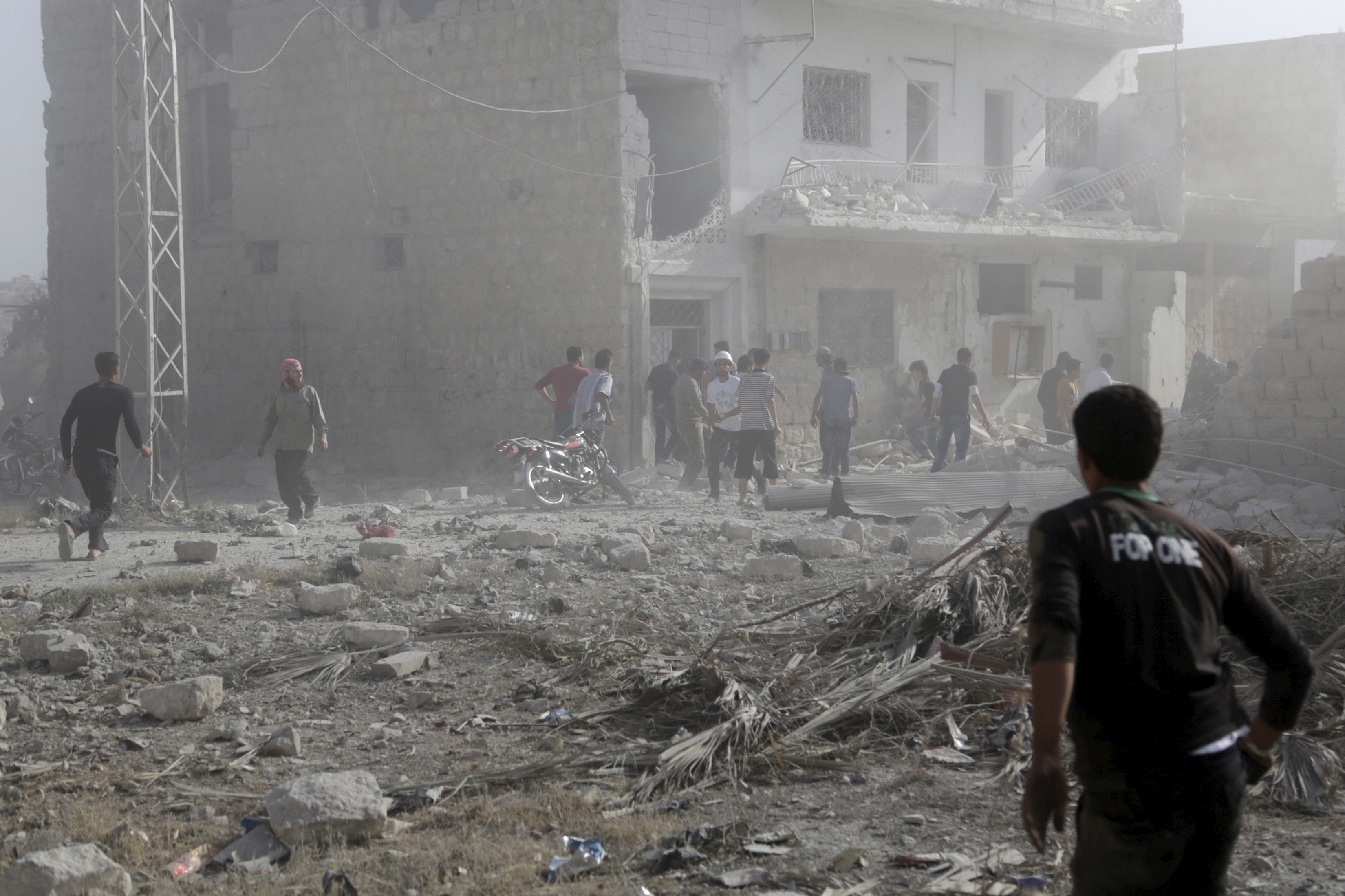 Residents inspect a site damaged by what activists said was a barrel bomb dropped by forces loyal to Syria's president Bashar Al-Assad in Maarat Al-Nouman, south of Idlib, June 8, 2015.