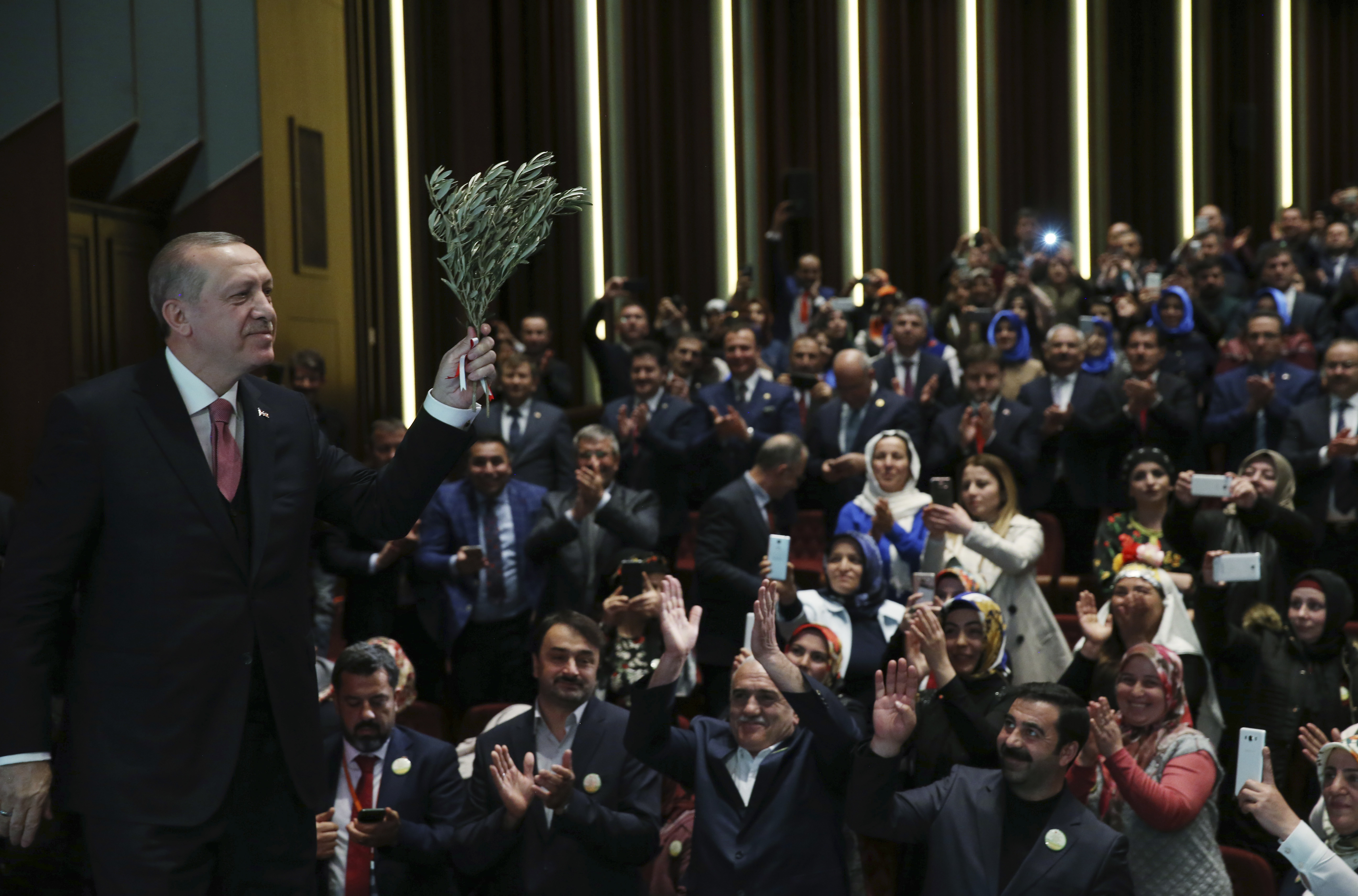 Turkey's President Recep Tayyip Erdogan, holding an olive branch arrives to deliver a speech at an event in Ankara, Turkey, Feb. 20, 2018.