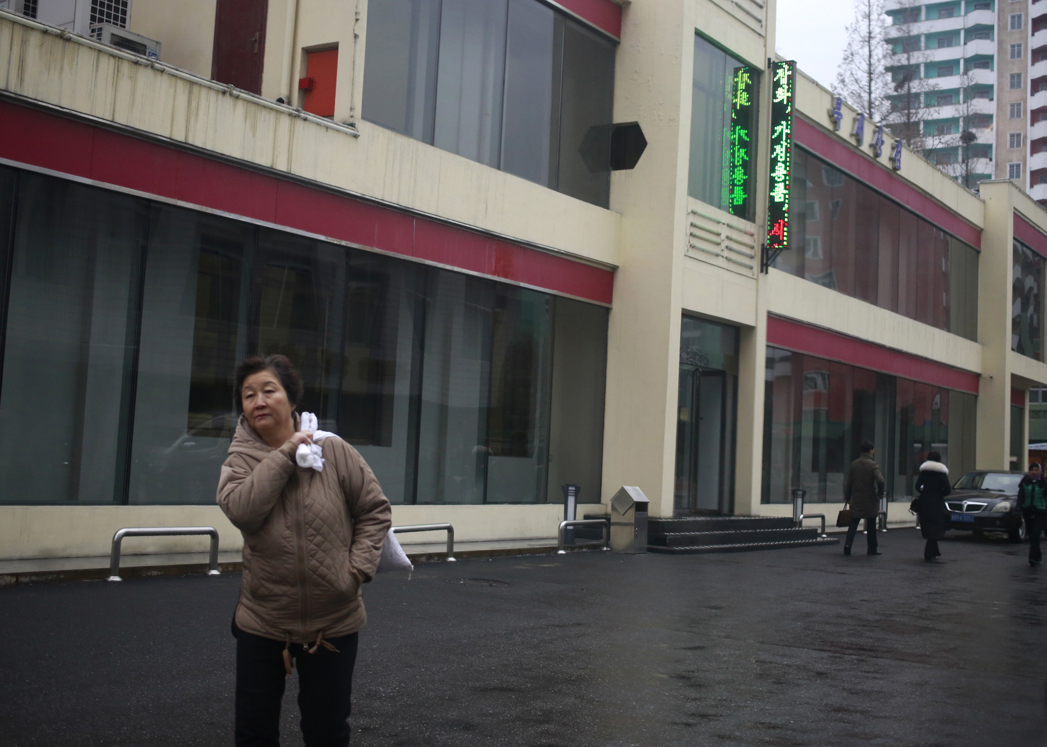 "FILE - In this Dec. 21, 2018, photo, a North Korean woman walks outside Bugsae Shop, also known as the ""Singapore Shop,"" in Pyongyang. Business is booming at such shops, which sell everything from Ukrainian vodka to brand-name knock-offs from China. ..."