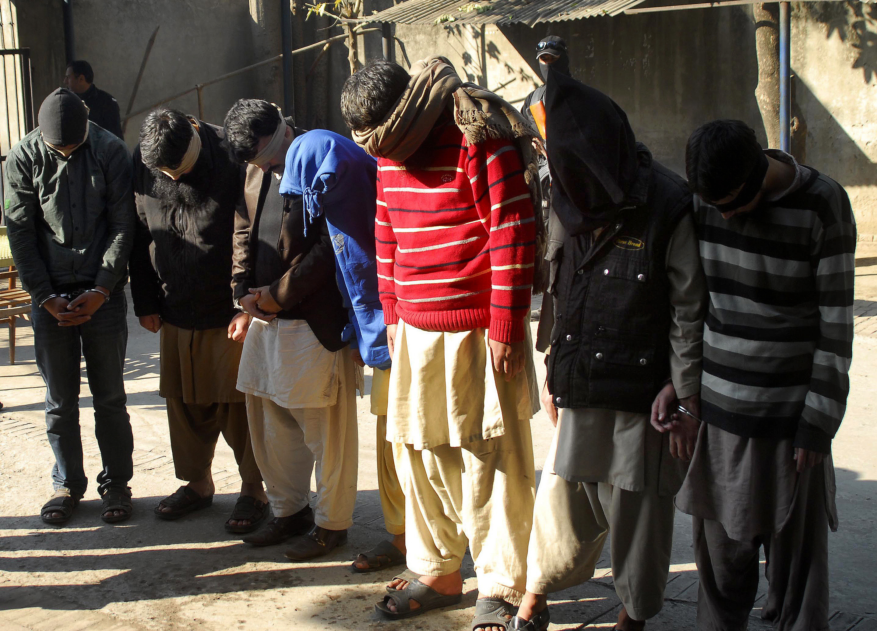 Pakistani suspects allegedly affiliated with the Islamic State group, wait to appear in the anti-terrorist court, in Gujranwala, Pakistan, on Dec. 29, 2015. Pakistani counter terrorism officials raided a home and detained 13 local militants who were ...
