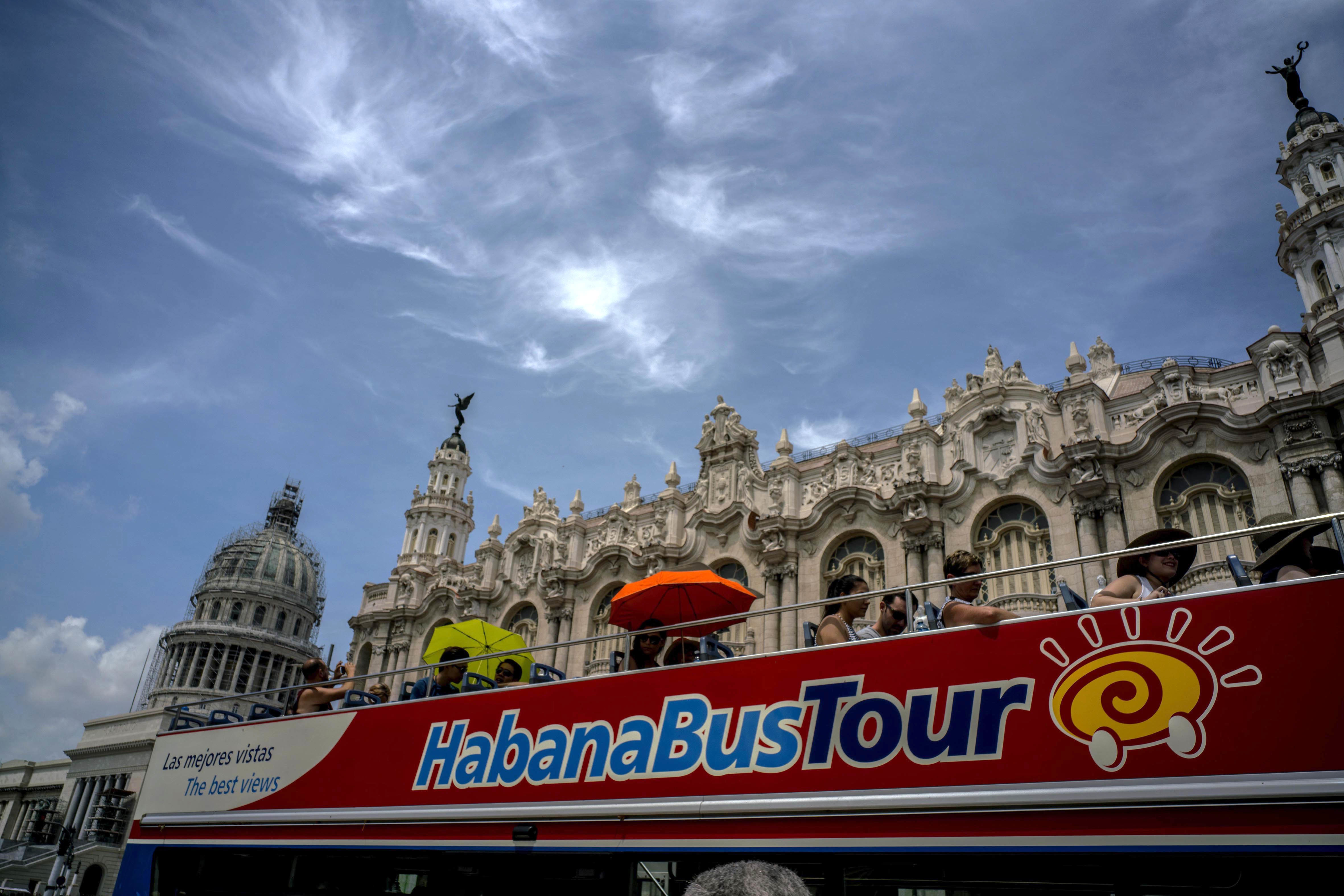FILE - In this June 17, 2017, photo, tourists ride a tour bus in front of the Capitolio in Havana, Cuba.