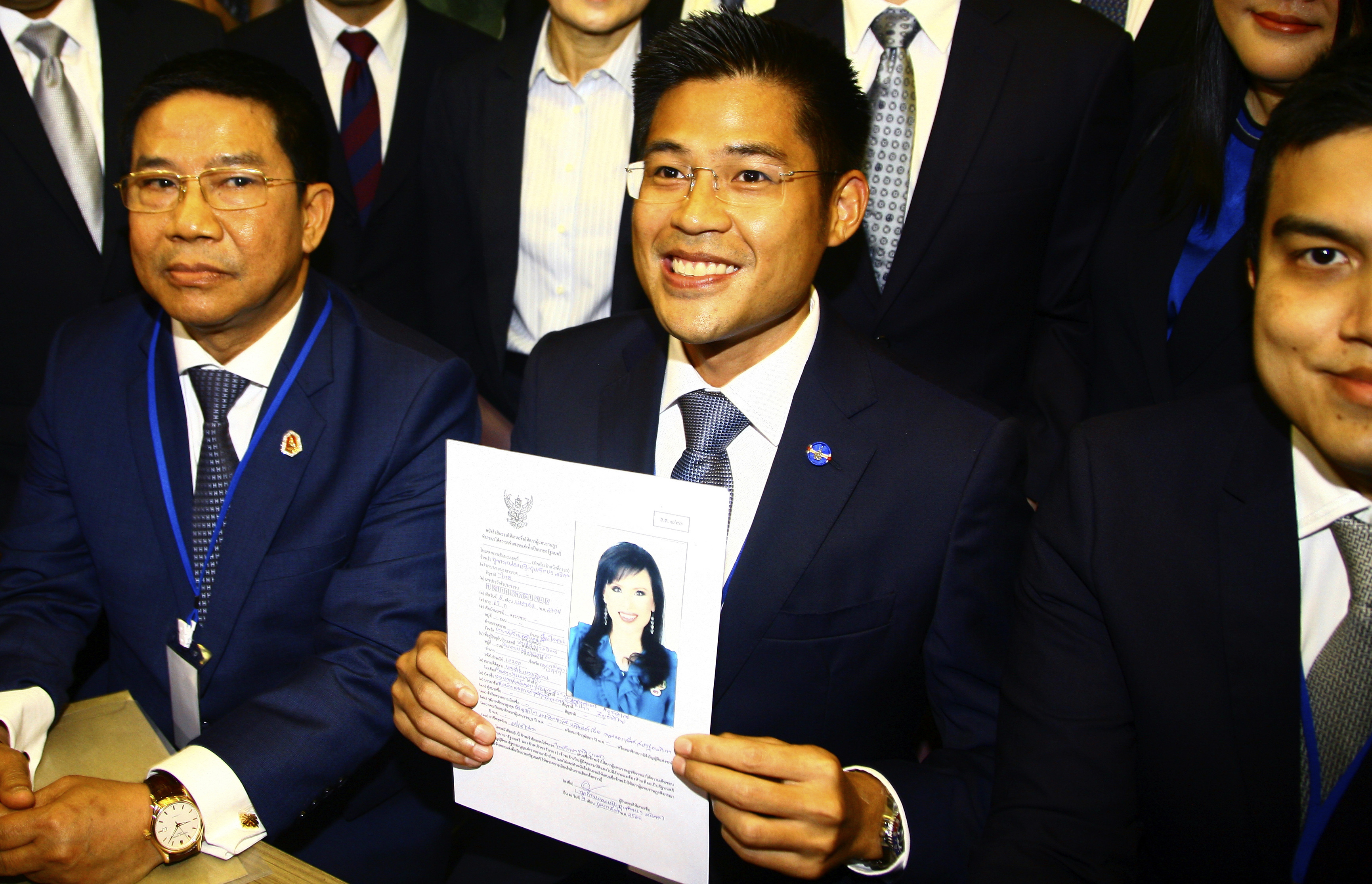 Leader of Thai Raksa Chart party Preecha Pholphongpanich, center, holds a picture of Princess Ubolratana at election commission of Thailand in Bangkok, Feb. 8, 2019. The political party has selected the princess as its nominee to serve as the next pr...