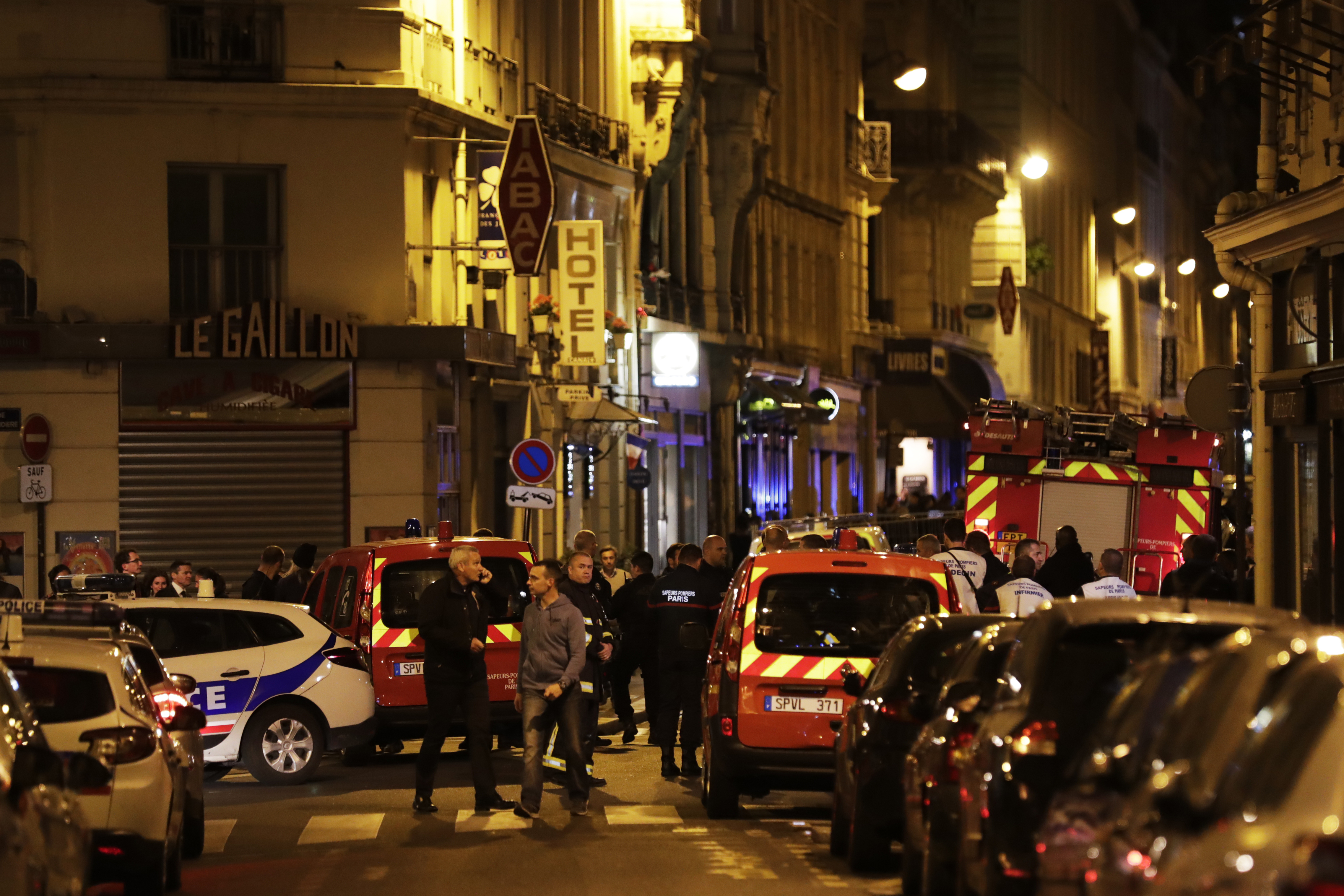 Policemen and emergency service members stand in a blocked street in Paris after one person was killed and several injured by a man armed with a knife, who was shot dead by police, May 12, 2018.