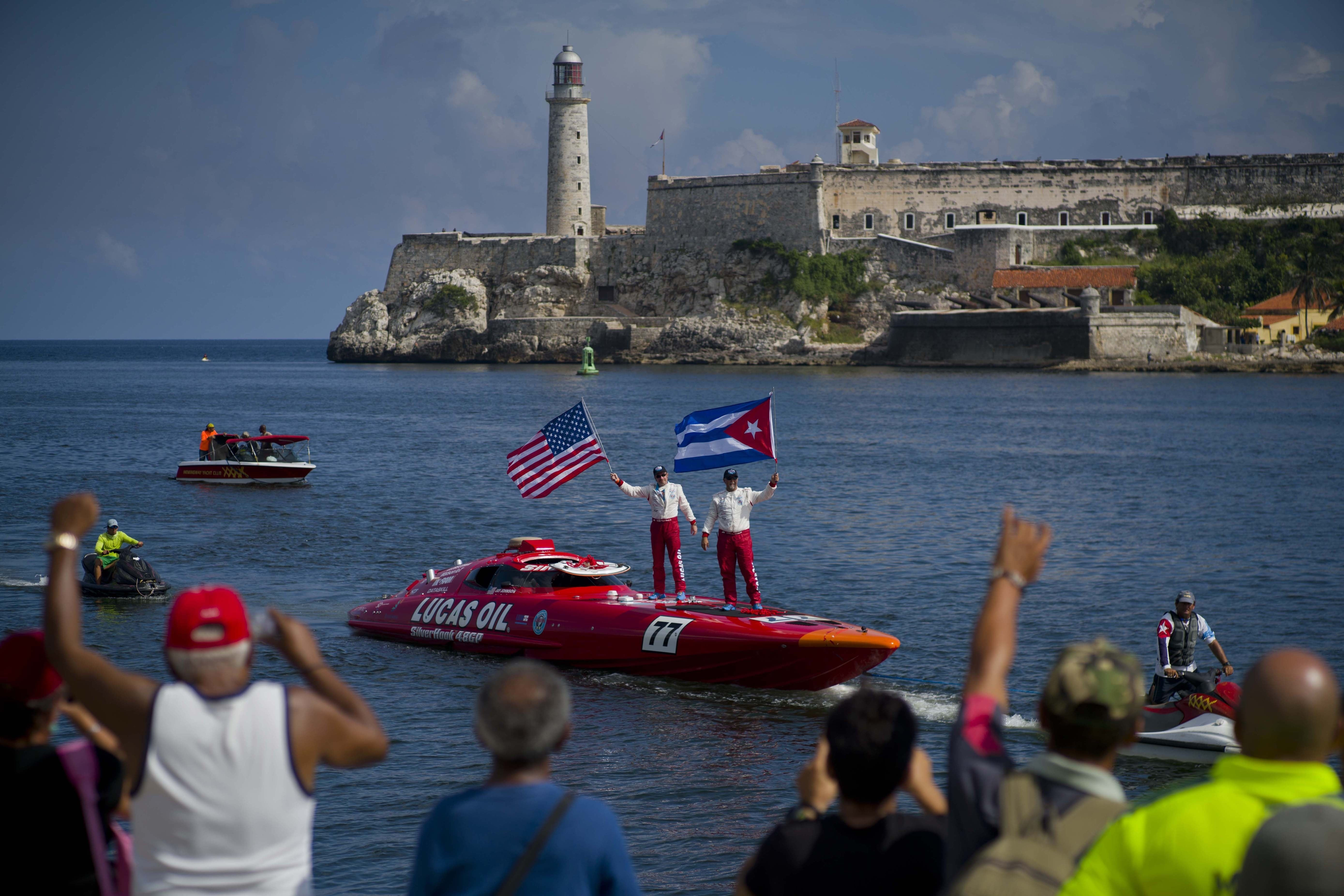 """Tourists stand aboard their speedboat, backdropped by """"El Morro"""" castle, in Havana, Cuba, Thursday, Aug. 17, 2017."""
