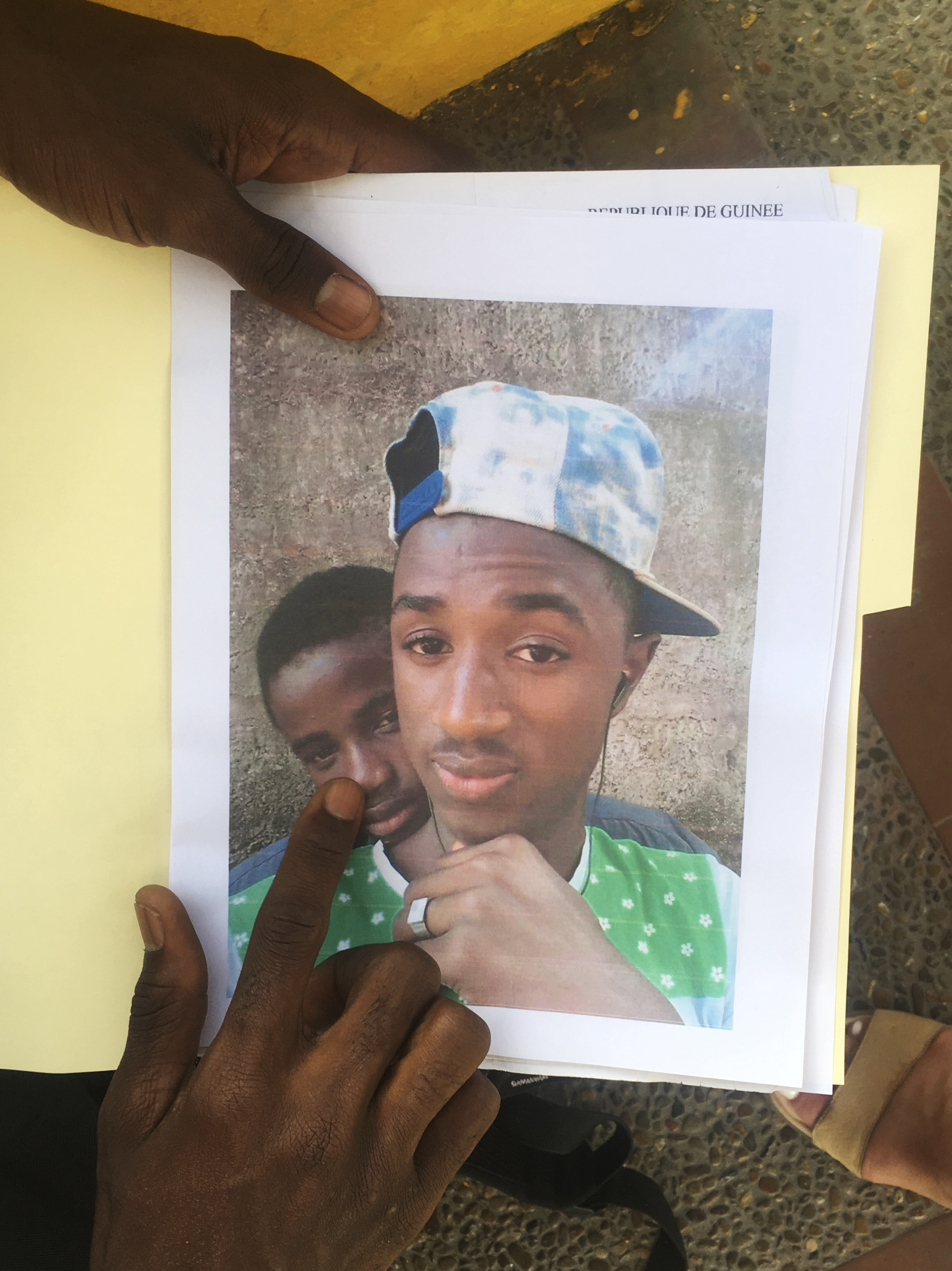 Mamadou Aliou Barry, who departed from his native Guinea in West Africa when he was 14, a few years ago, shows a print of a selfie with his friend while waiting for entry to the U.S. on the Gateway Bridge in Matamoros, Mexico, which connects to Brown...