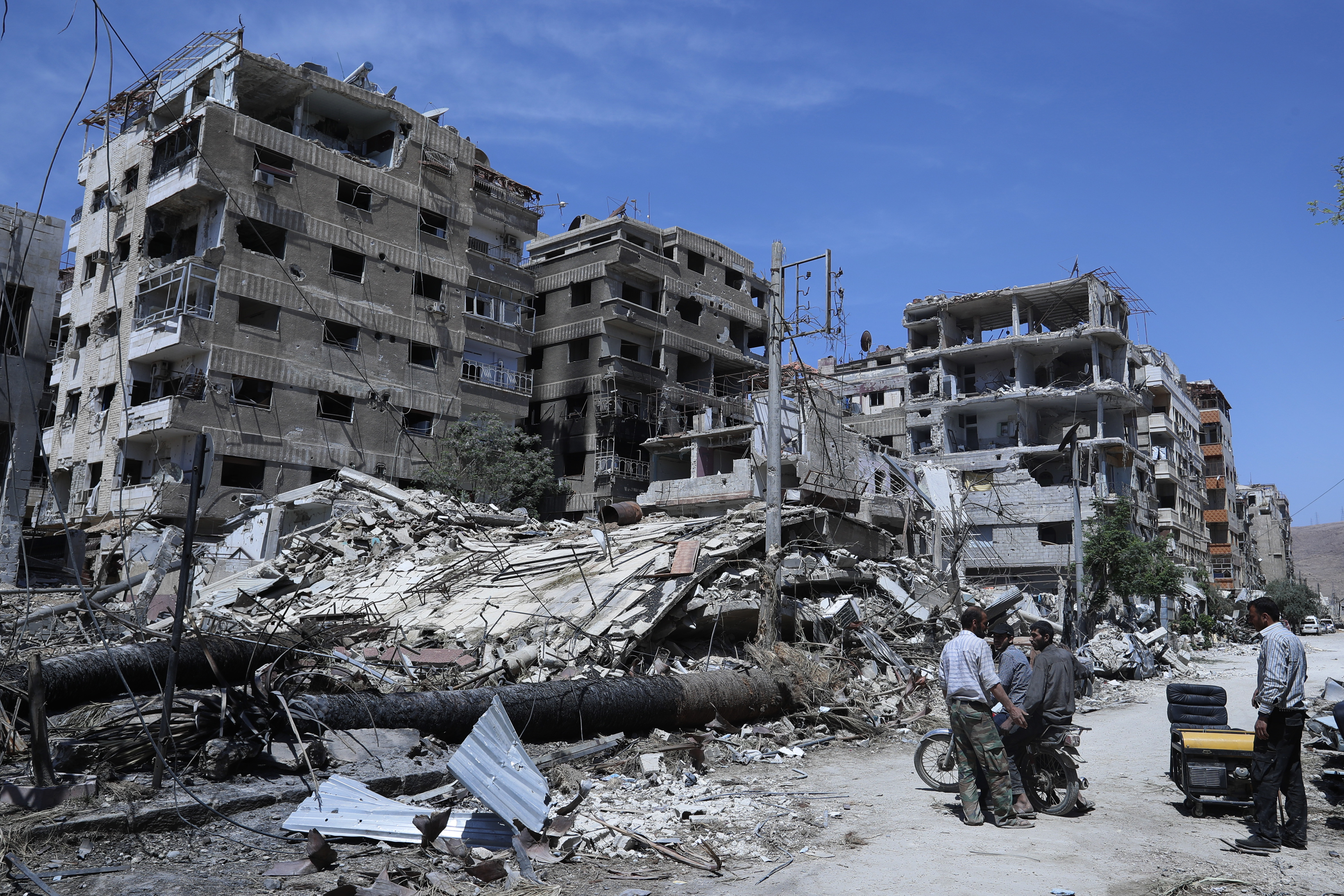 People stand in front of damaged buildings, in the town of Douma, the site of a suspected chemical weapons attack, near Damascus, Syria, April 16, 2018.