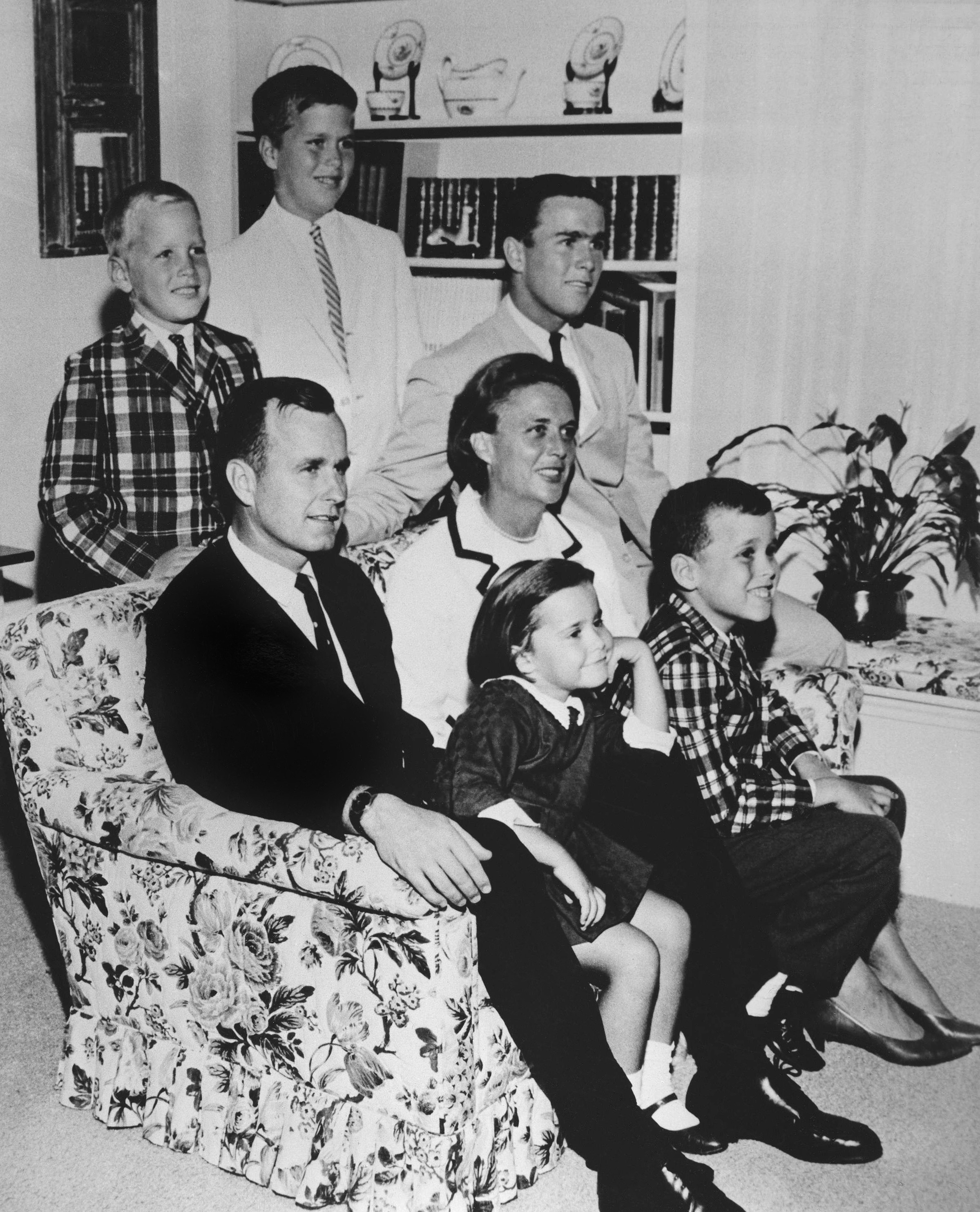 George H.W. Bush sits on couch with his wife Barbara  and their children in 1964.