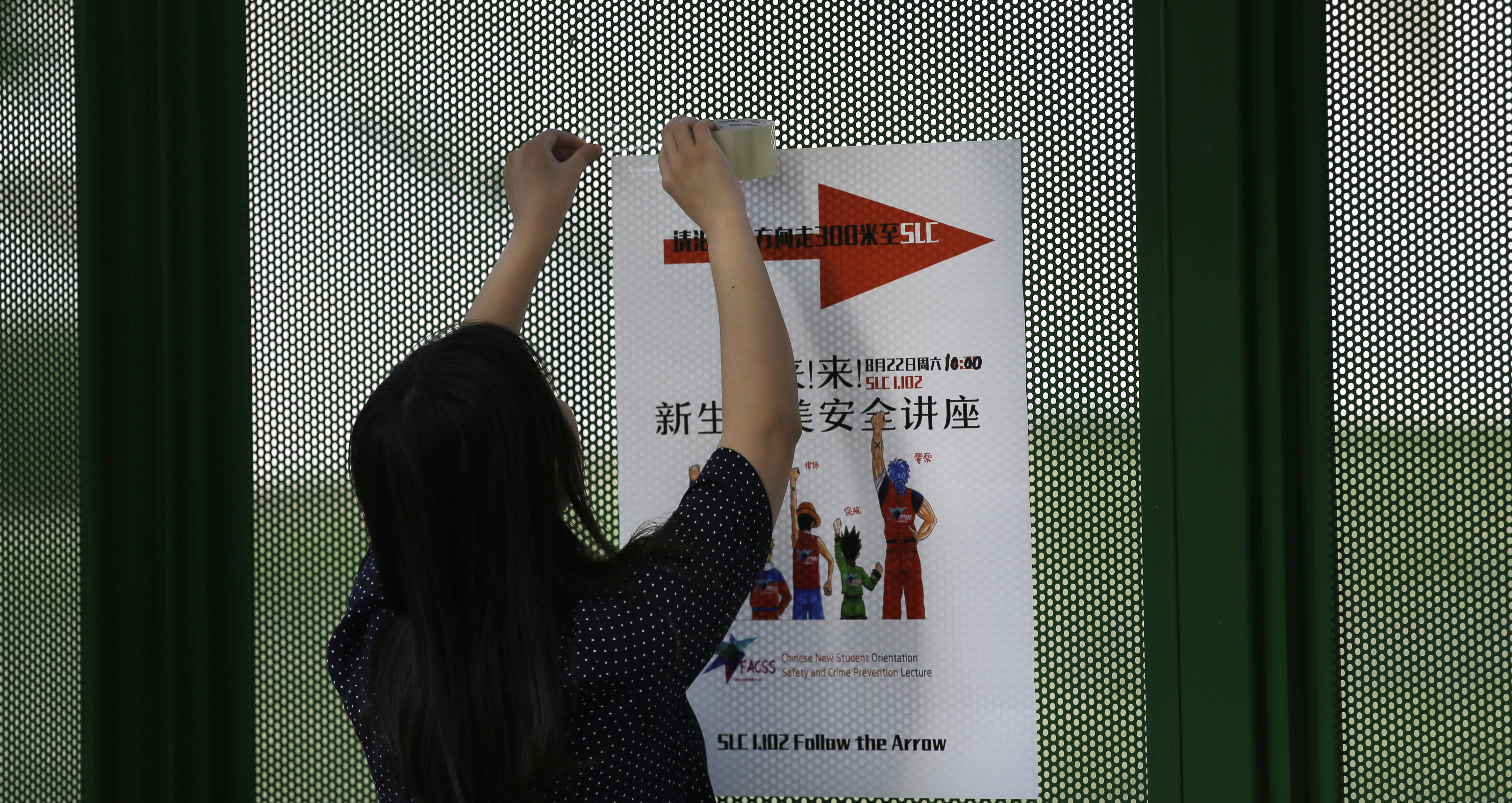 FILE - Ailu Xu, a graduate student from China, posts a sign directing Chinese students to a new student orientation meeting at the University of Texas at Dallas in Richardson, Texas, Aug. 22, 2015.