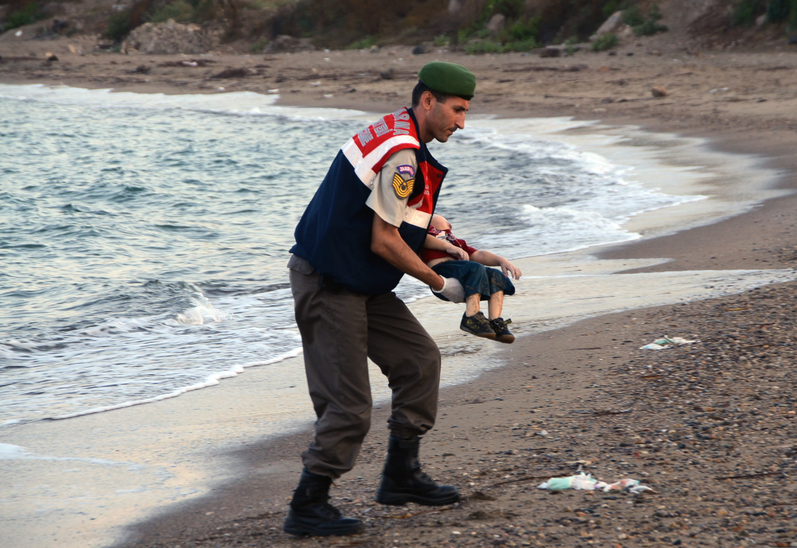 A paramilitary police officer carries the lifeless body of an unidentified migrant child, lifting it from the seashore near the Turkish resort of Bodrum, Sept. 2, 2015.