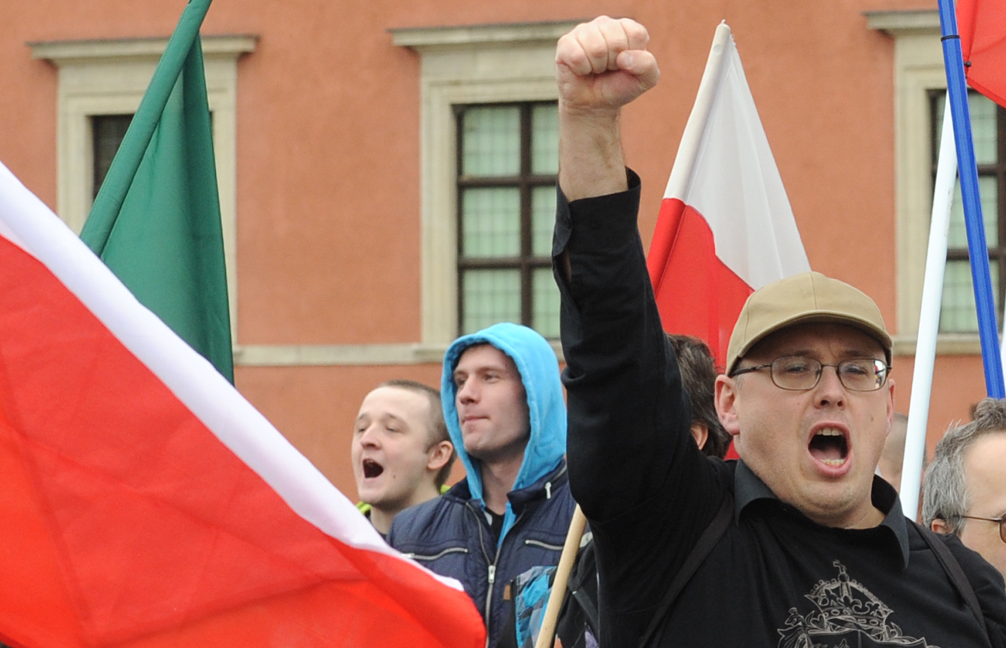 A supporter of a right wing organization gestures, as others shout slogans during an anti-migrant rally in Warsaw, Poland, Sept. 26, 2015.