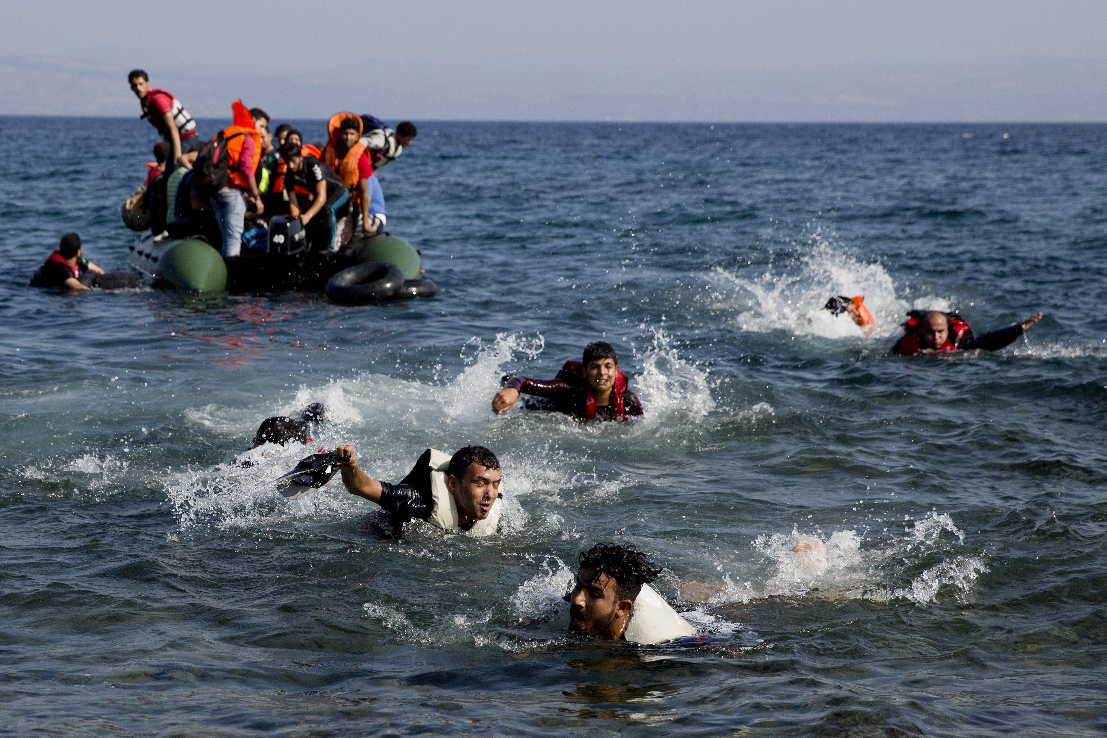 Migrant whose boat stalled at sea while crossing from Turkey to Greece swim to approach the shore of the island of Lesbos, Greece, Sept. 20, 2015.