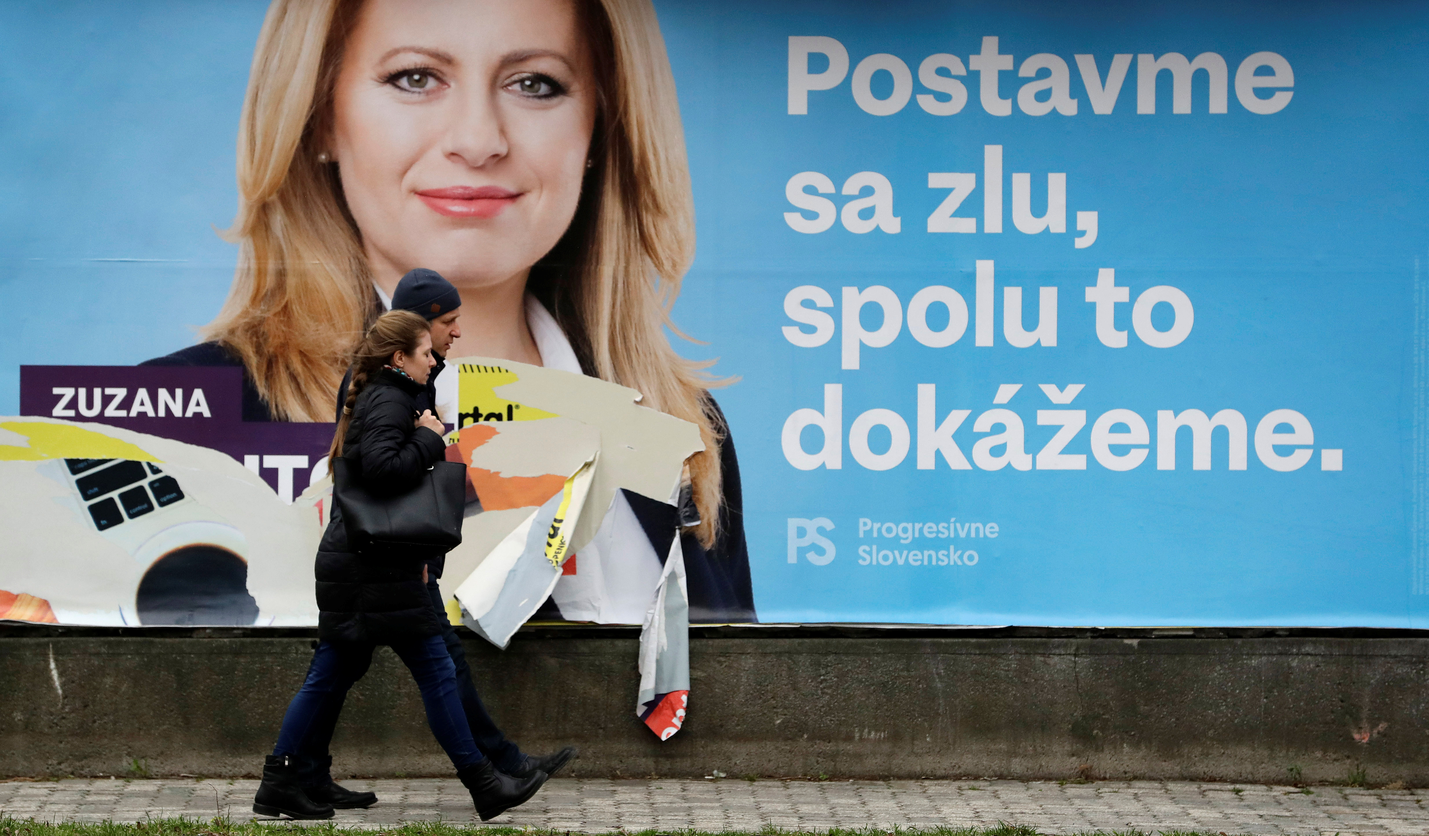 """People walk past an election poster of Slovakian presidential candidate Zuzana Caputova in Bratislava, Slovakia, March 15, 2019. The poster reads: """"President for fair Slovakia. Stand up against evil, together we can do it."""""""