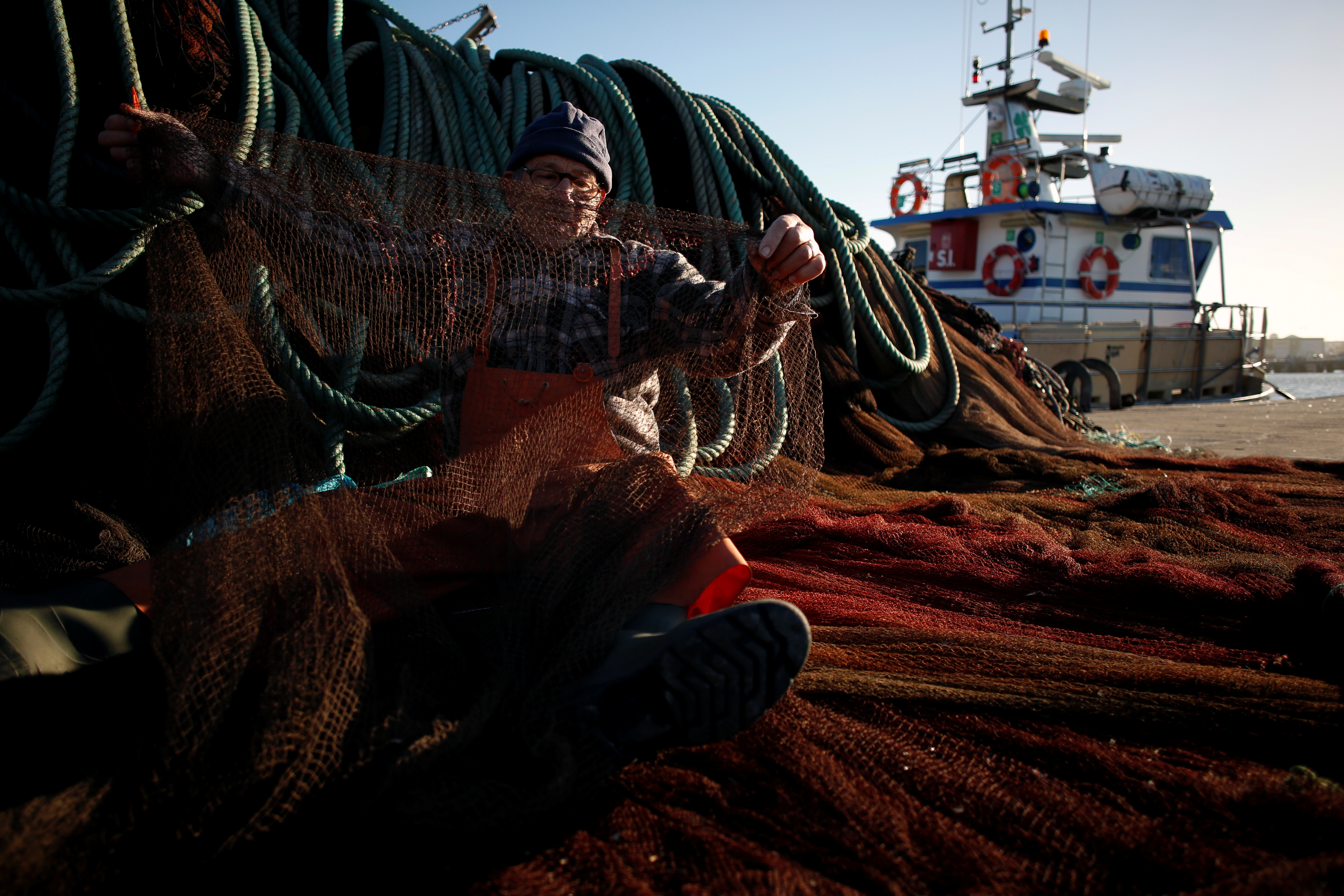Fisherman Erbes Martins sews his net in the port of Peniche, Portugal, Feb. 6, 2018.