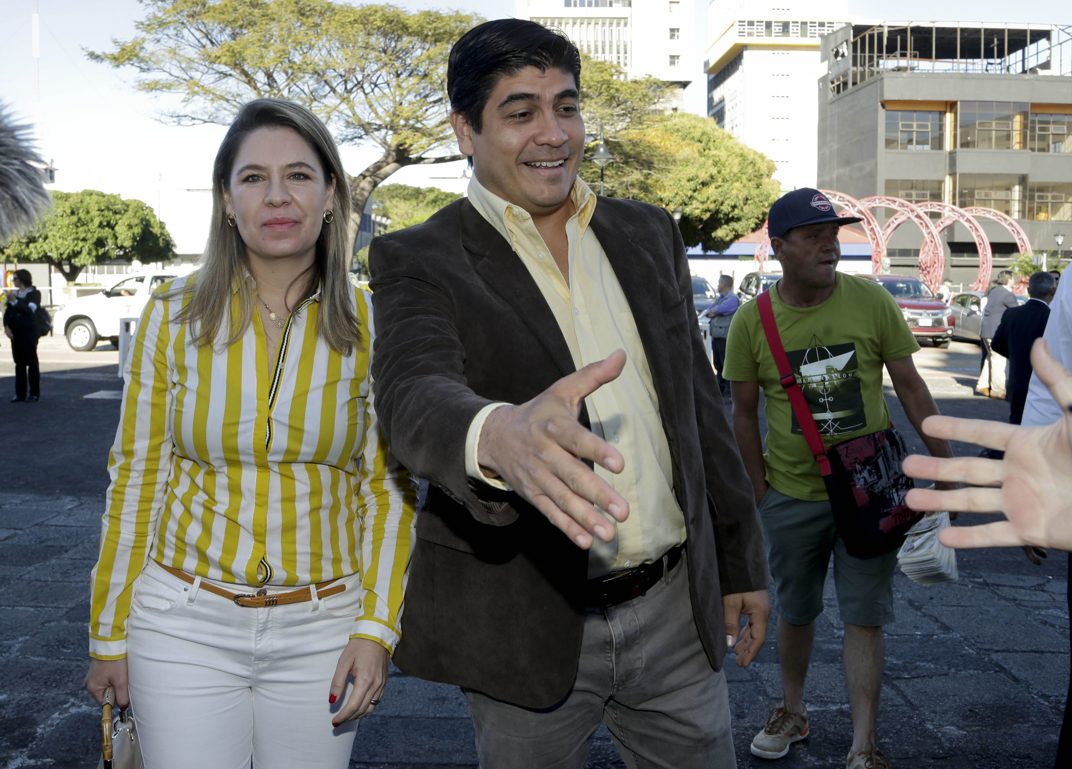 Presidential candidate Carlos Alvarado, right, with the Citizen Action party, greats a supporter as he arrives to a Mass at La Soledad church before casting his ballot during general elections in San Jose, Costa Rica,  Feb. 4, 2018.