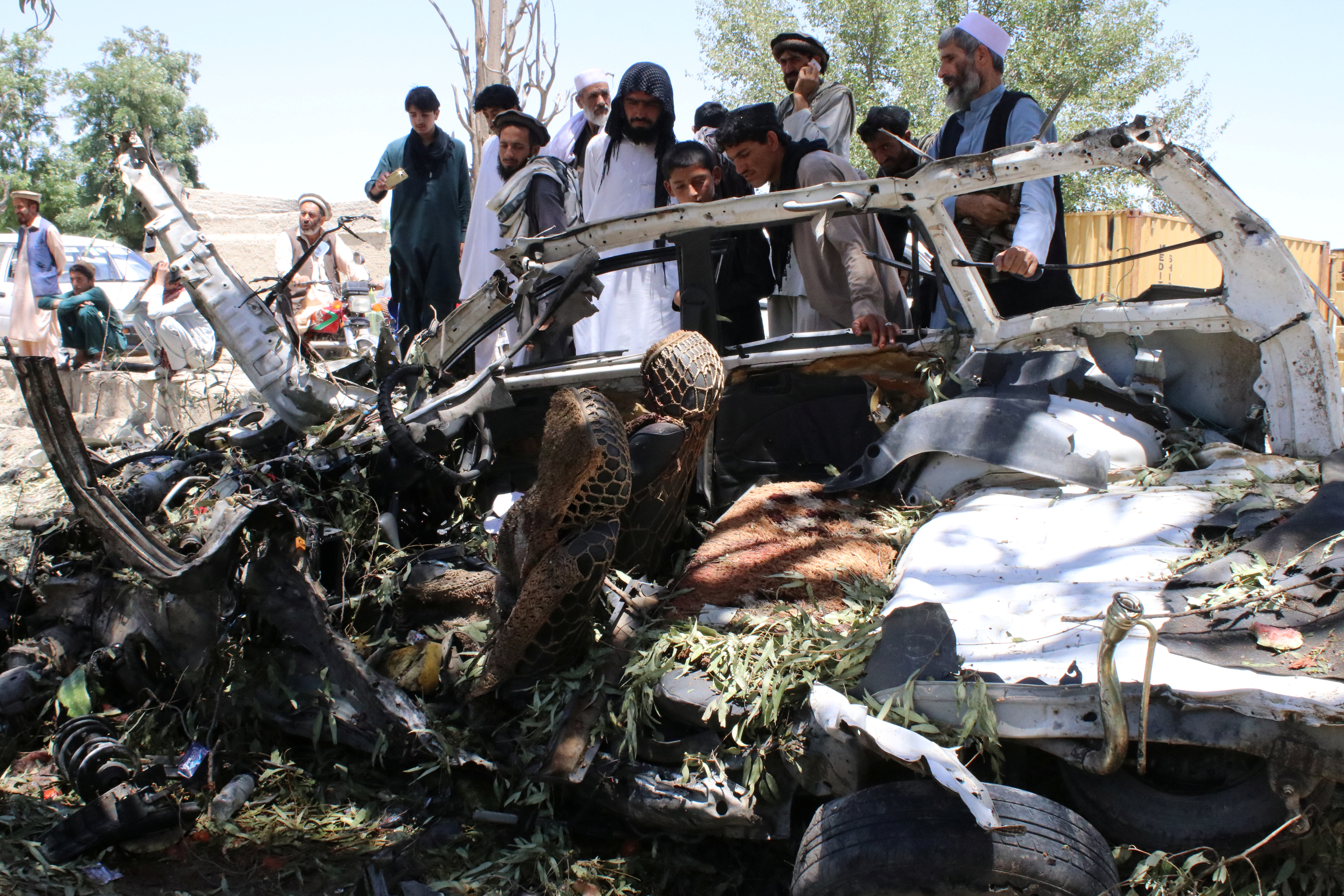 Afghan men inspect a car damaged in a suicide car bomb attack in Khost province, May 27, 2017.