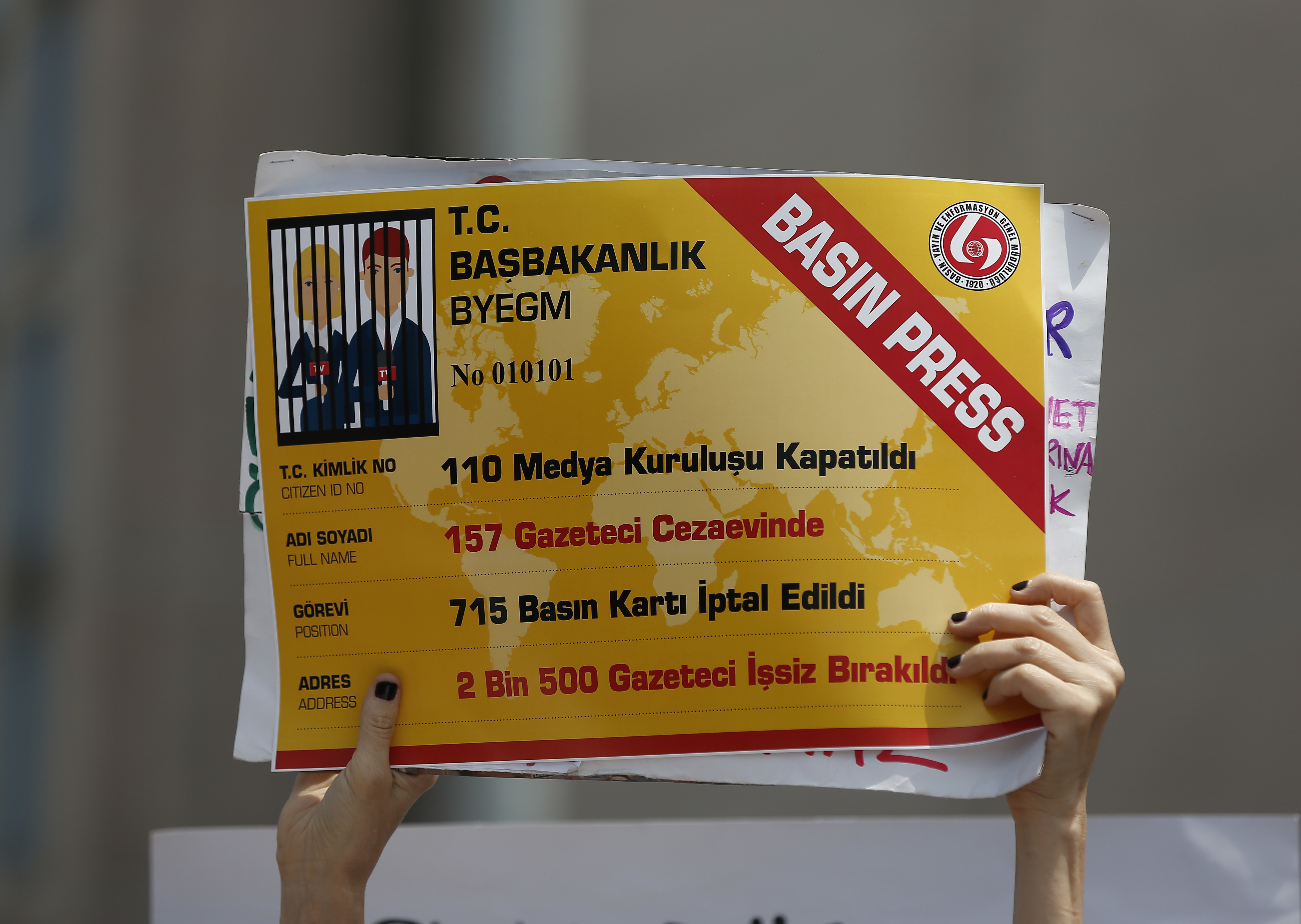 """An activist holds a placard, made to look like a press card, that reads """" 110 media organizations closed,157 journalists jailed, 715 press cards cancelled, 2.500 journalists fired """" outside the court in Istanbul, July 28, 2017."""