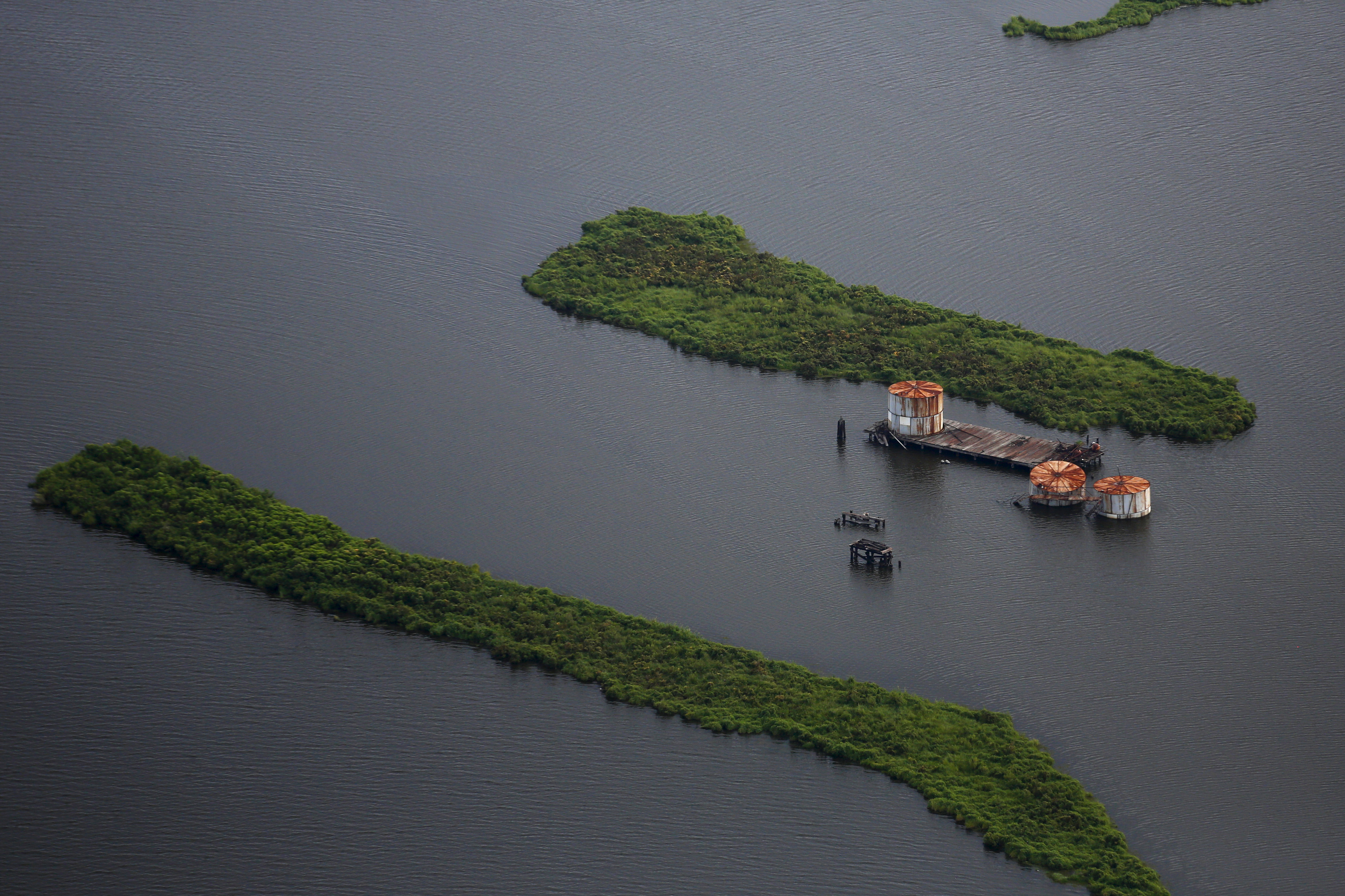 FILE - Old oil tanks are seen in an area affected by Hurricane Katrina on the Mississippi river delta, New Orleans, Louisiana, Aug. 19, 2015.